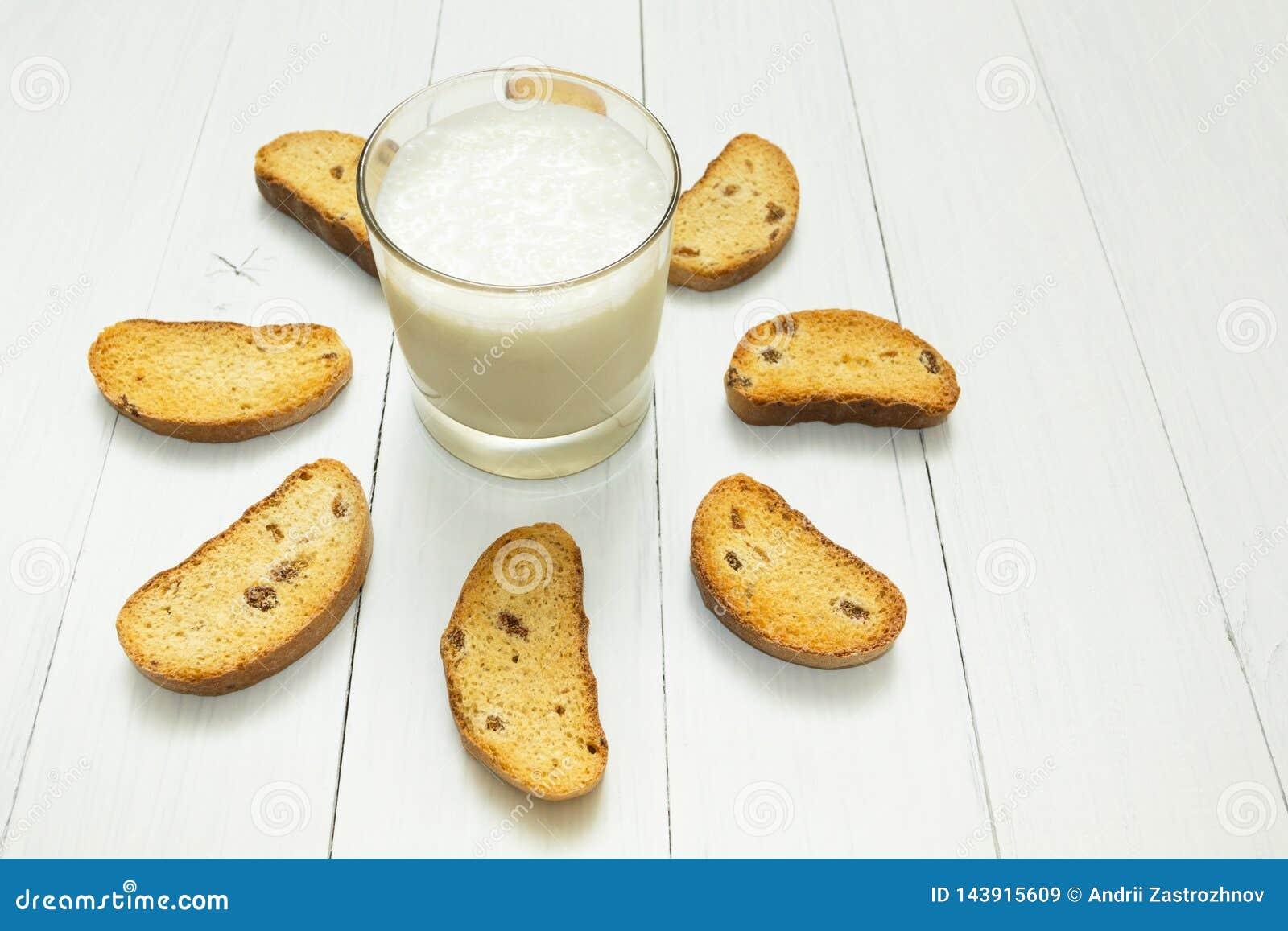 Nourriture saine, yaourt aigre dans une tasse en verre et biscuits avec des raisins secs sur une table blanche