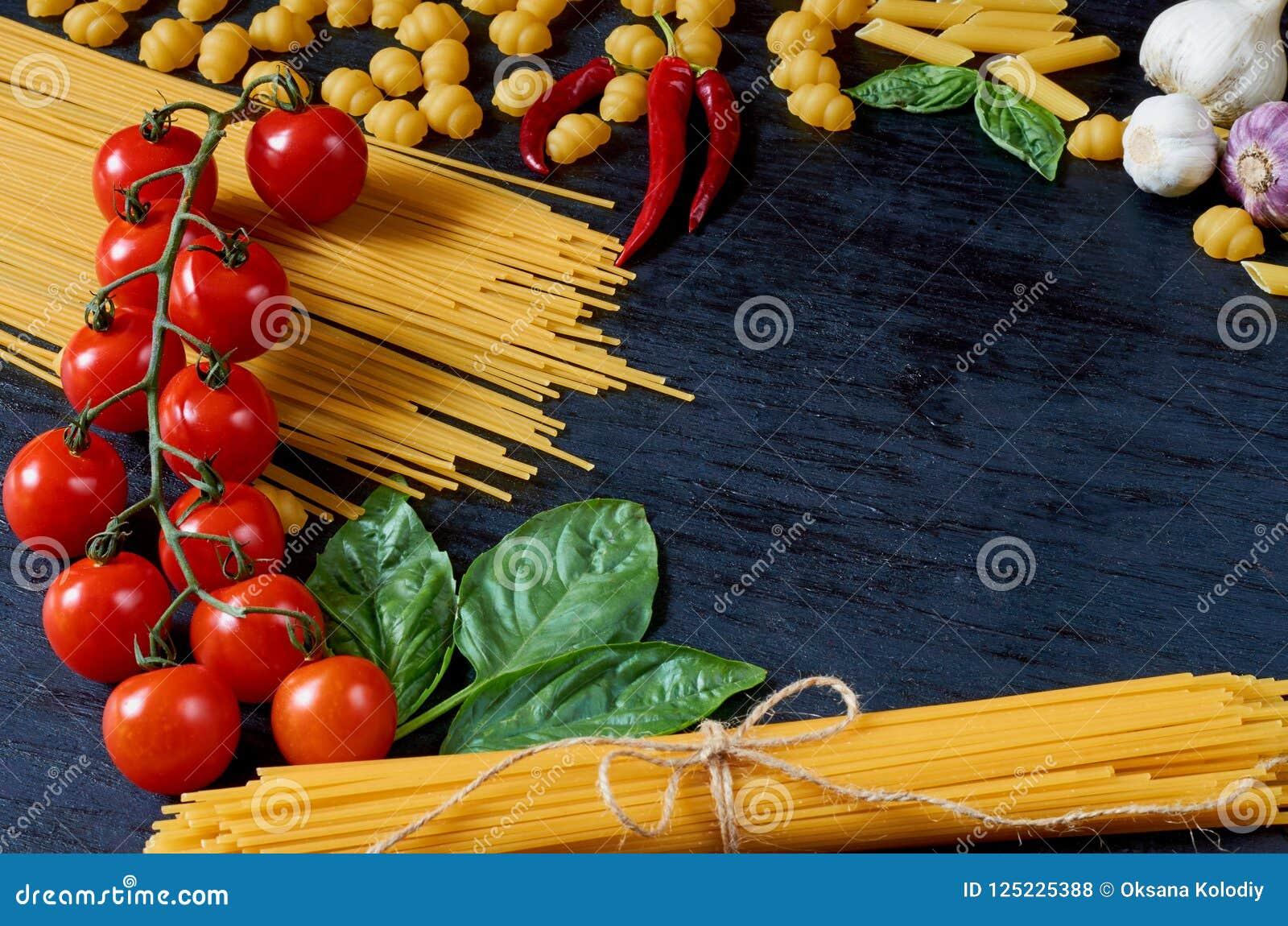 Nourriture traditionnelle italienne, épices et ingrédients pour faire cuire comme basilic, tomates-cerises, poivre de piment, ail