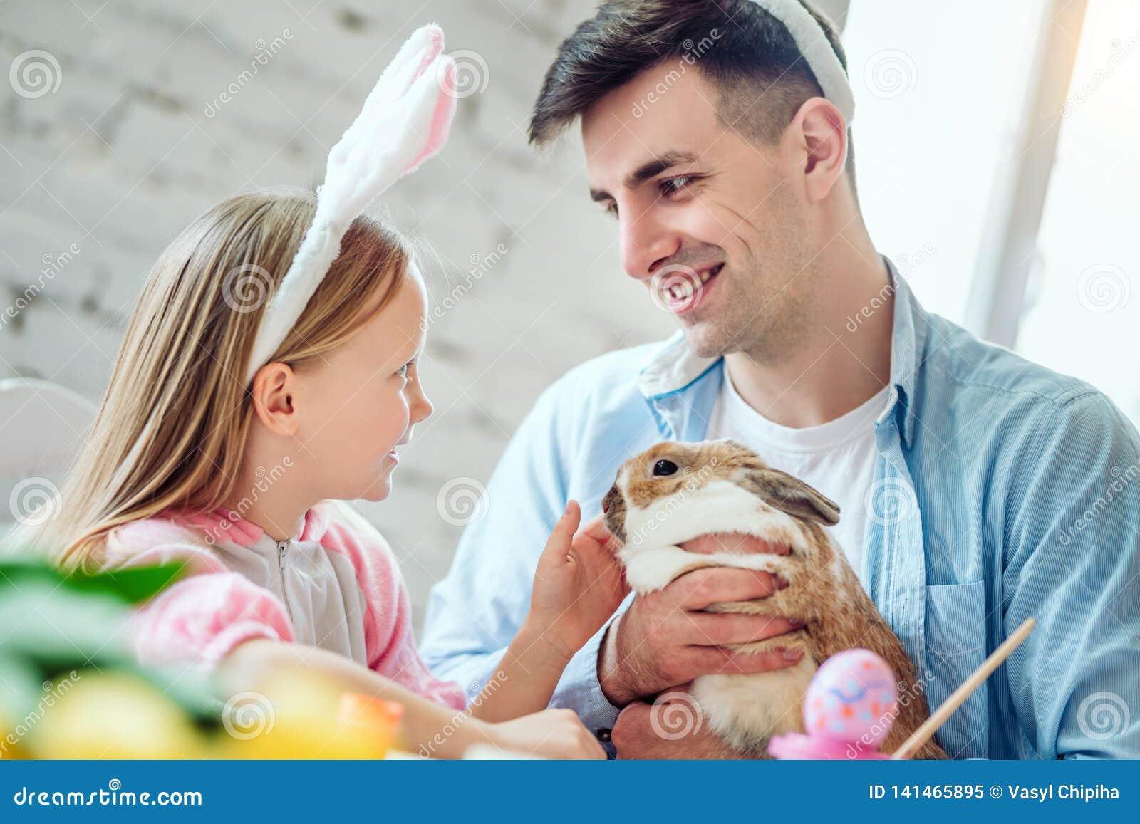 Nous aimons de belles traditions Les oeufs de peinture de maman et de fille, papa tient un lapin décoratif à la maison