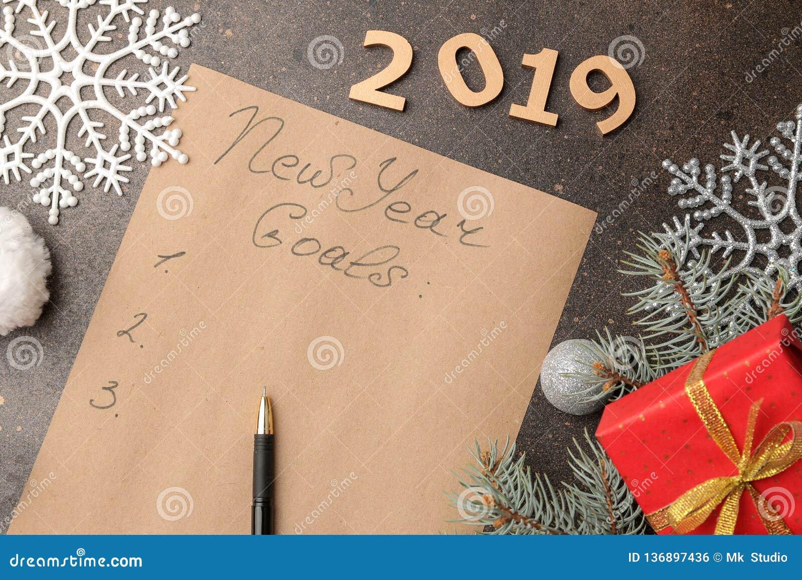 Nouveaux buts 2019 Texte sur un morceau de papier avec un stylo et décoration de nouvelle année sur un fond foncé