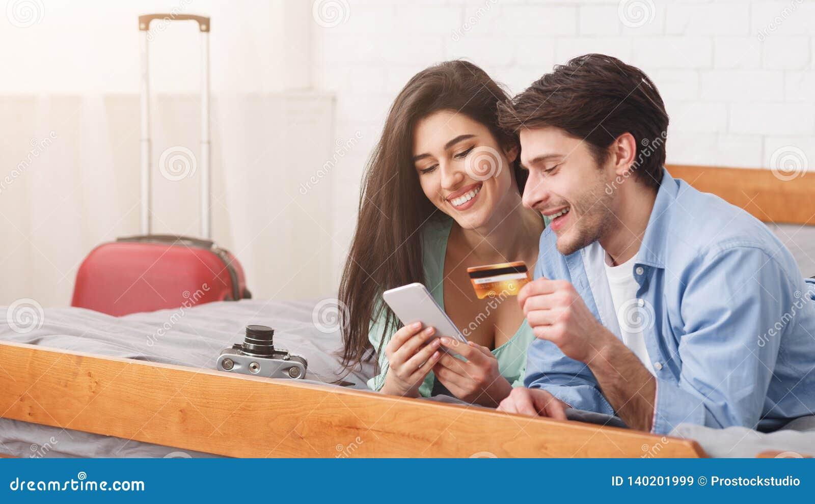 Nouveaux mariés réservant l hôtel utilisant le téléphone et la carte de crédit
