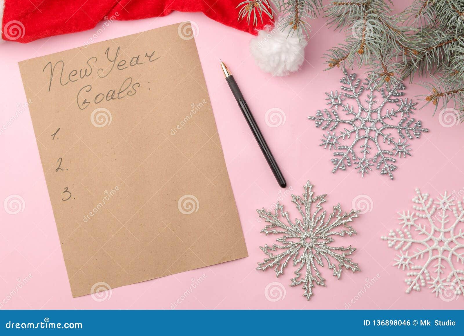 Nouvelles années de buts 2019 Texte sur un morceau de papier avec un décor de nouvelle année et un stylo sur un fond rose lumineu