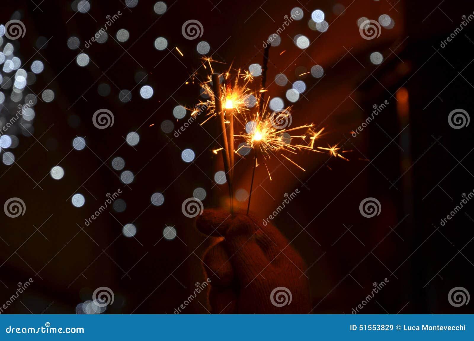 Nouvelles années de célébration de la veille avec les feux d artifice tenus dans la main de cierge magique