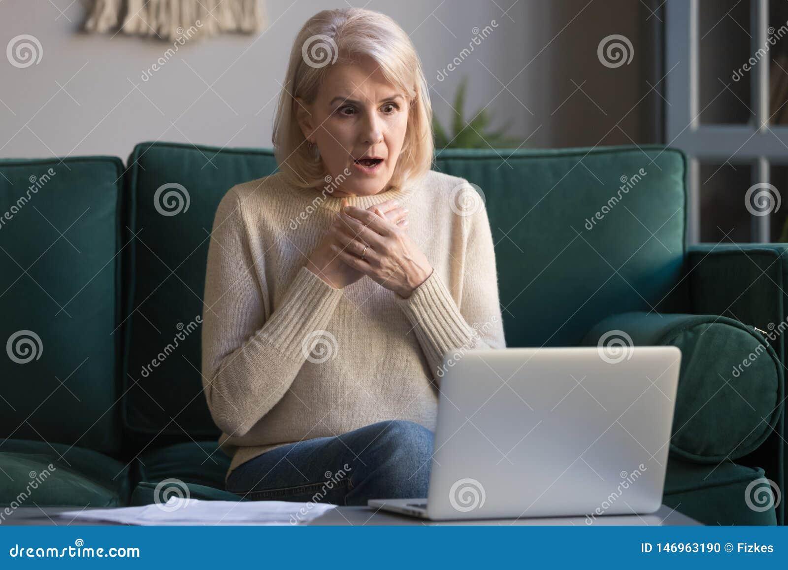 Nouvelles inattendues de lecture choquées de femme mûre d une chevelure grise sur l ordinateur portable
