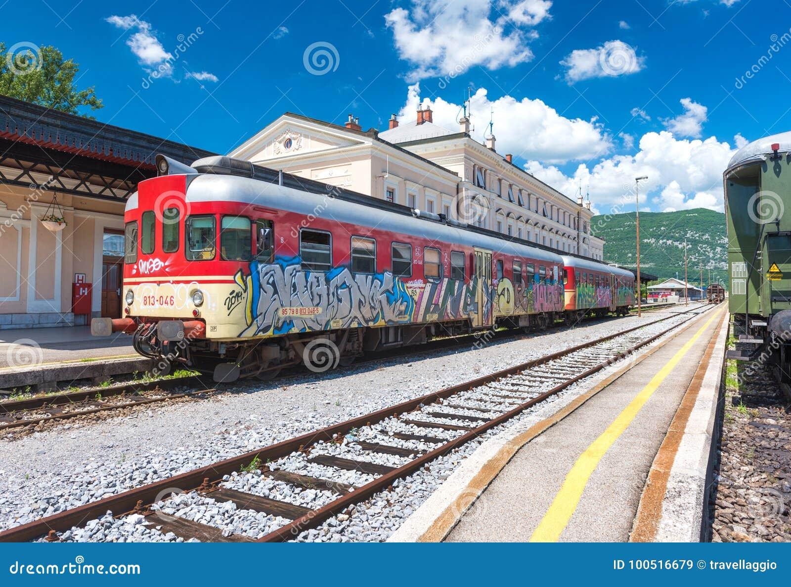 Nova Gorica, Slovenië: Rode trein met graffititribunes op sporen bij het station