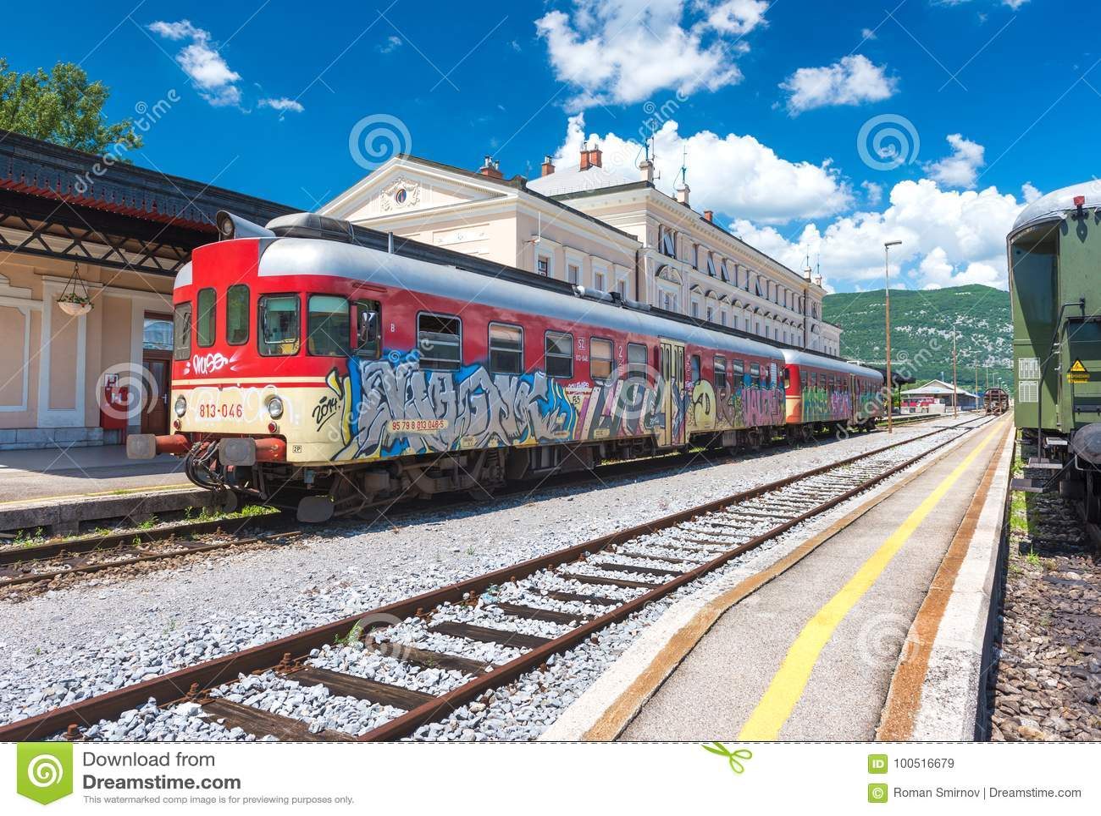 Nova Gorica Slovenien: Det röda drevet med grafitti står på spår på drevstationen