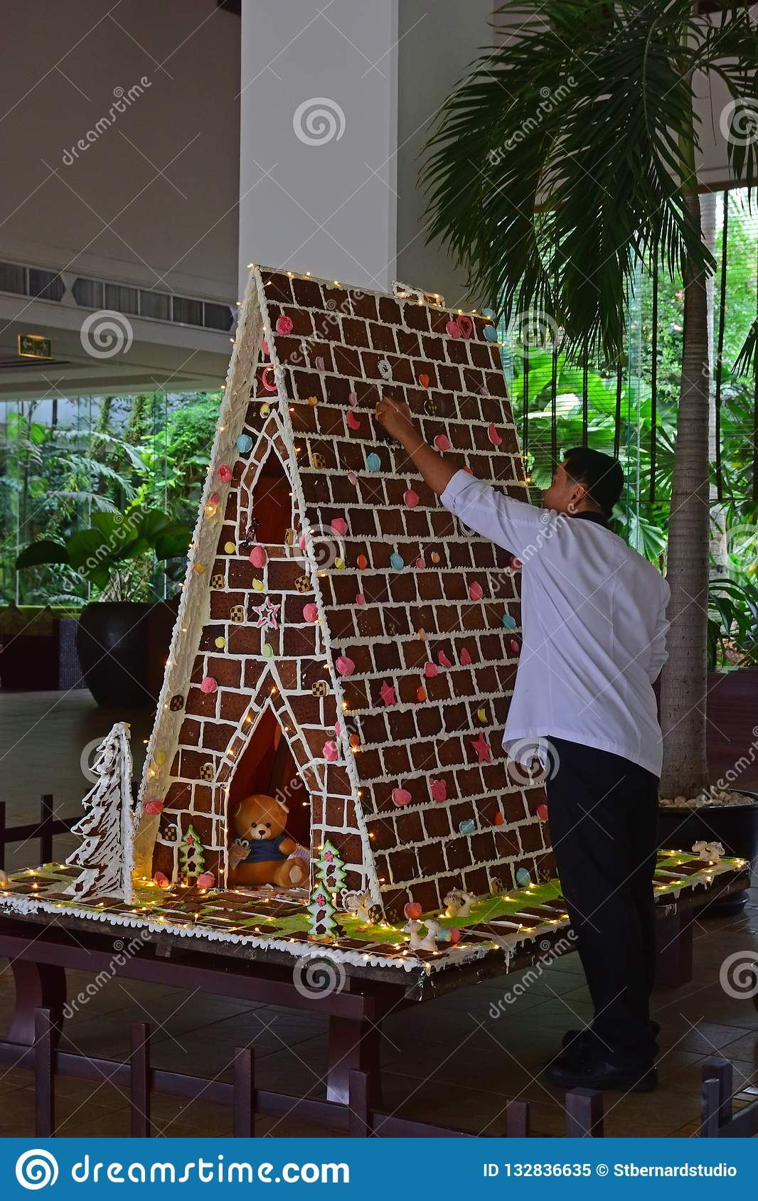 Man building large gingerbread house in a commercial setup