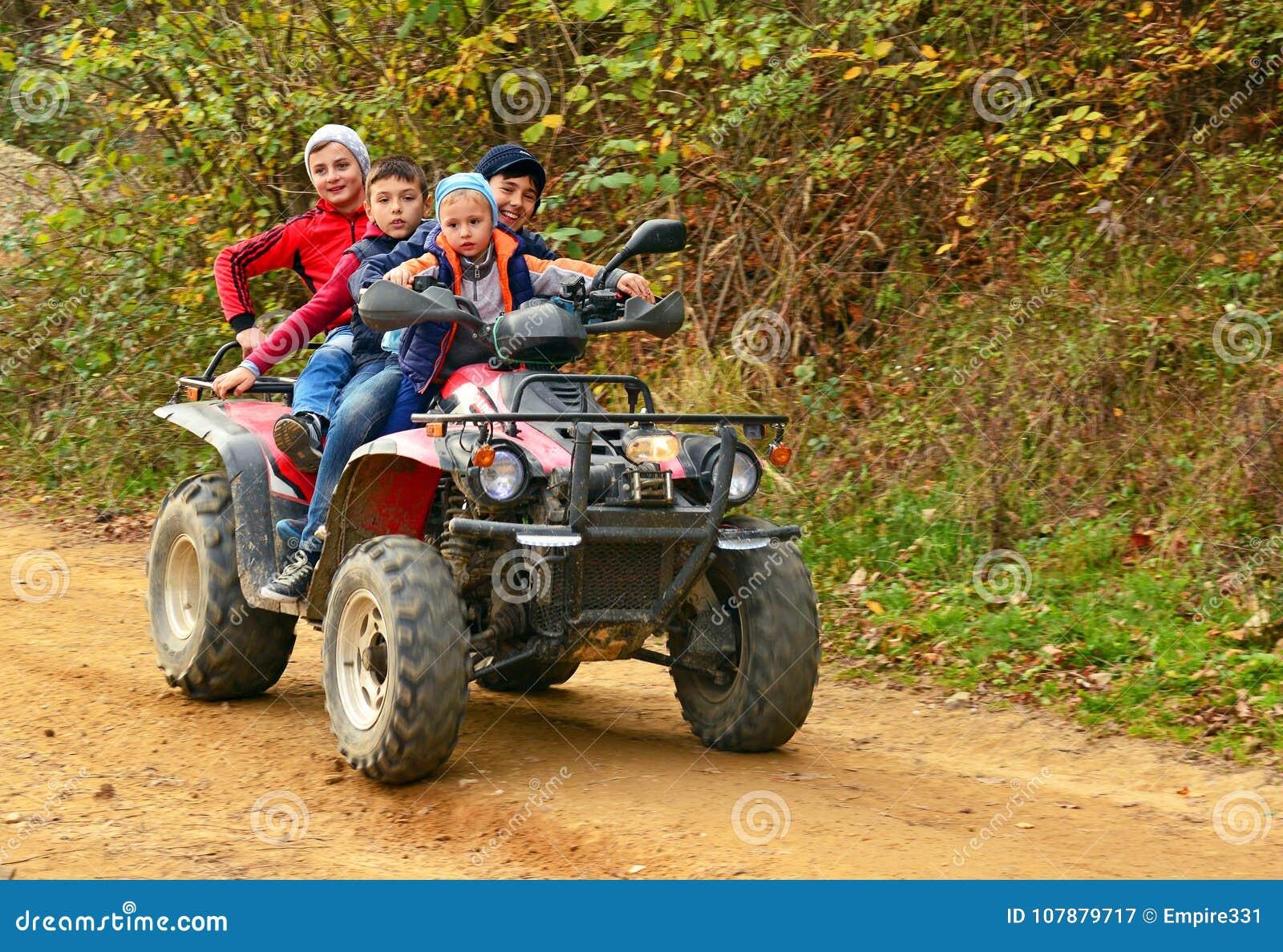 Kids on quad bike editorial photography  Image of boys