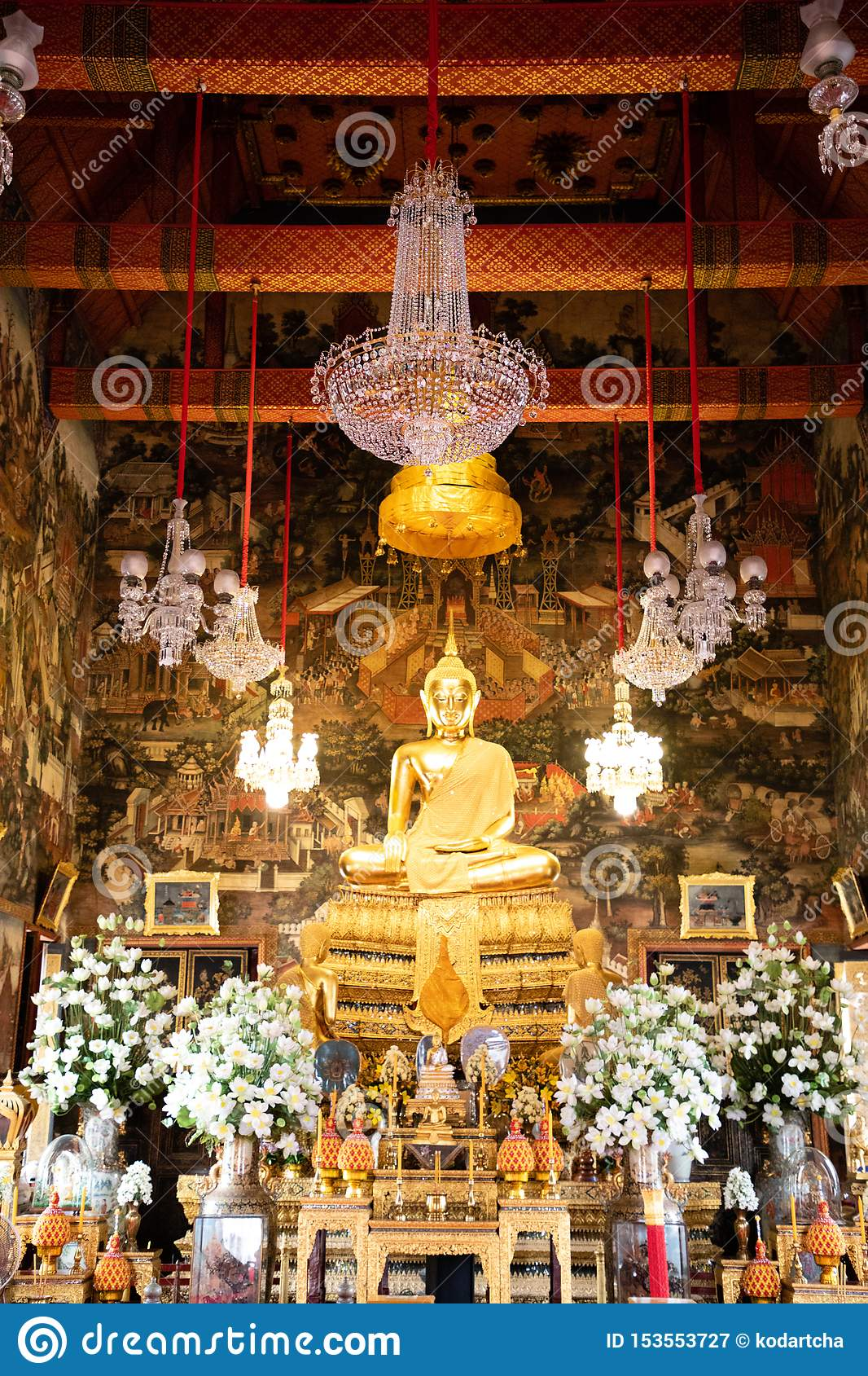 November 20th, 2018 - Bangkok THAILAND - Big golden Buddha surrounded by white orchids in thai temple