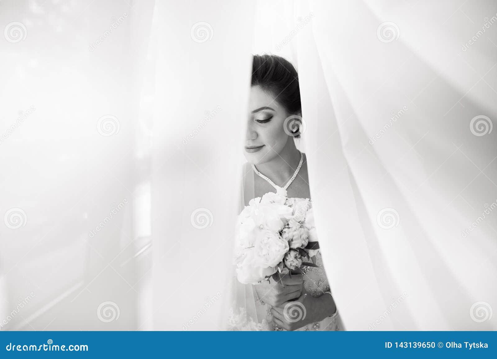 Novia atractiva hermosa en el vestido blanco que presenta debajo de la cortina