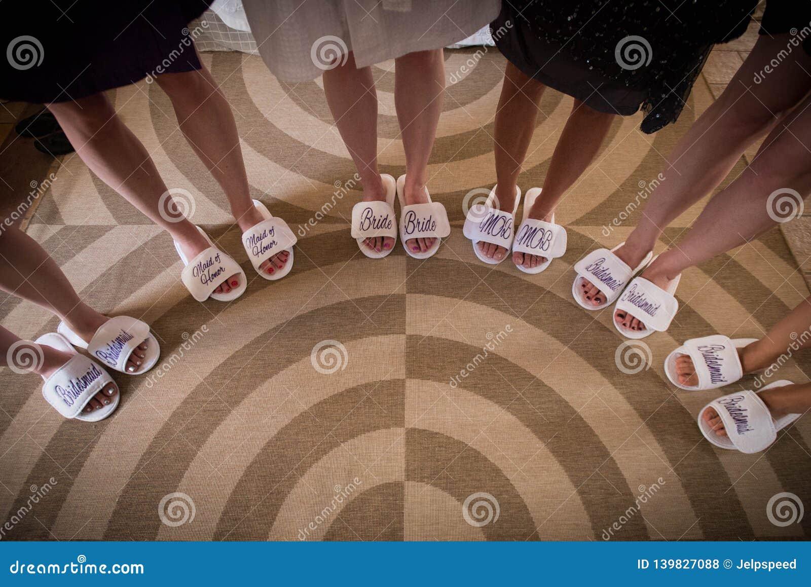 Novia con las muchachas en las sandalias nupciales agradables, piernas de la novia