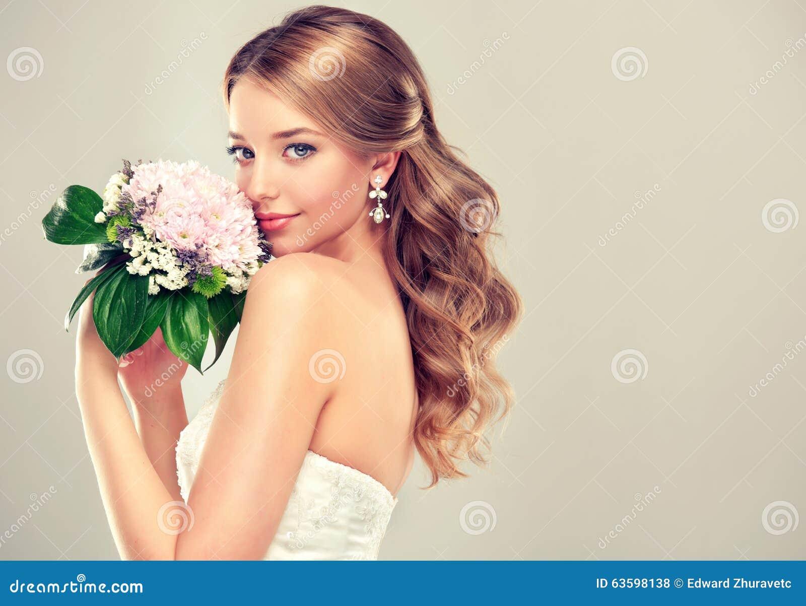 Novia de la muchacha en vestido de boda con el peinado elegante