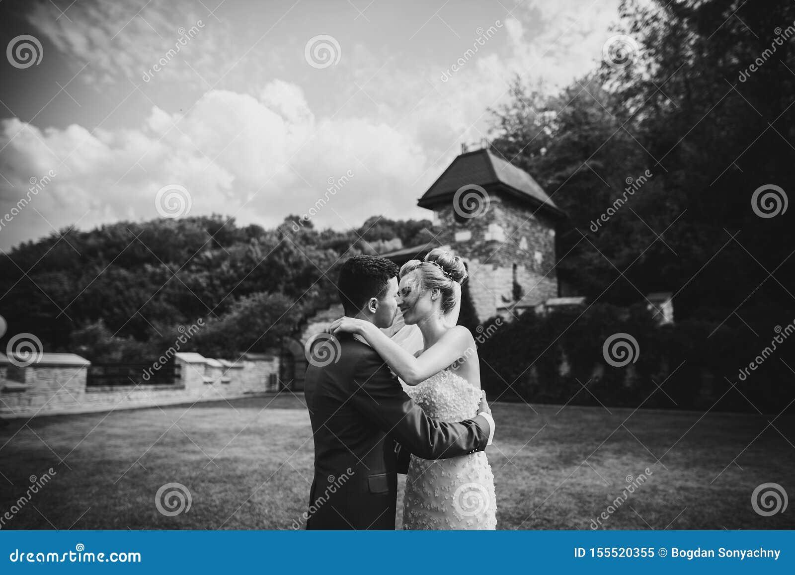 Novia elegante y novio que abrazan suavemente durante matrimonio cerca de casarse el pasillo de pétalos color de rosa Pares hermo