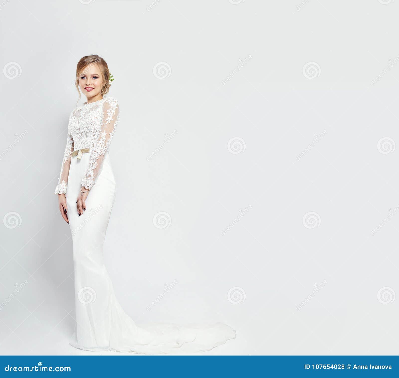 3b61bcd55 Novia en vestido de boda blanco largo en un fondo blanco Vestido lujoso en  un cuerpo del ` s de la mujer La muchacha se está preparando para casarse  Mujeres ...