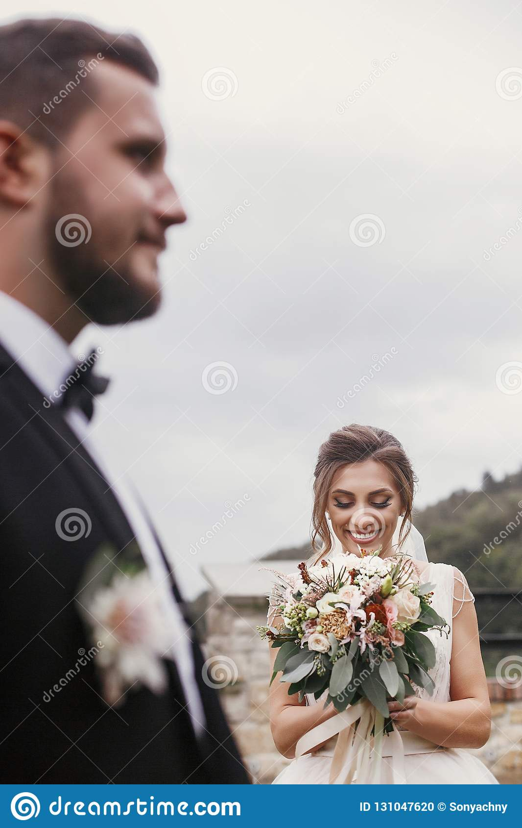 Novia feliz magnífica con el ramo moderno que mira groo elegante