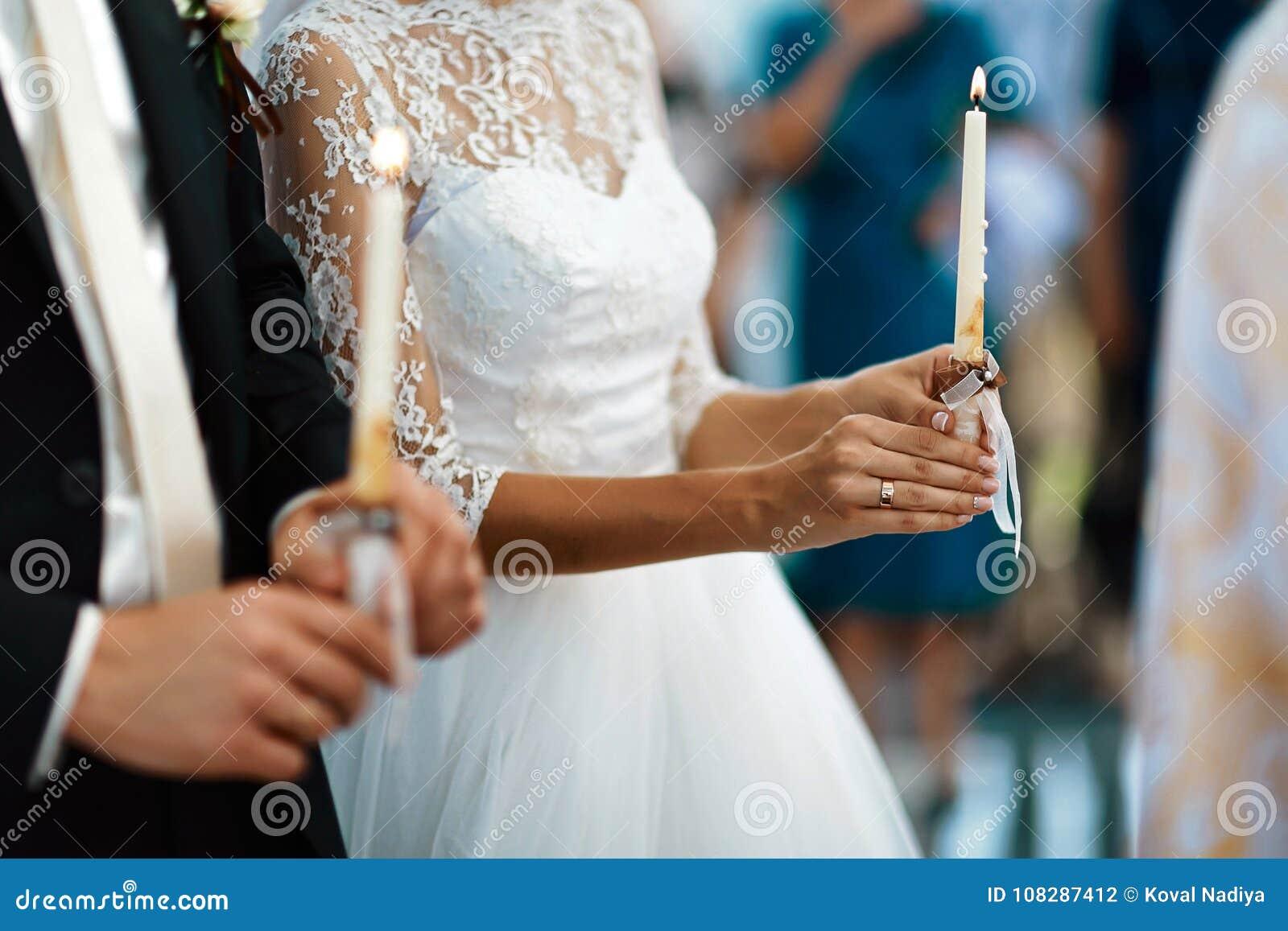 Novia feliz y novio elegante que llevan a cabo la ceremonia de boda de las velas, par de la boda en el matrimonio en iglesia, mom