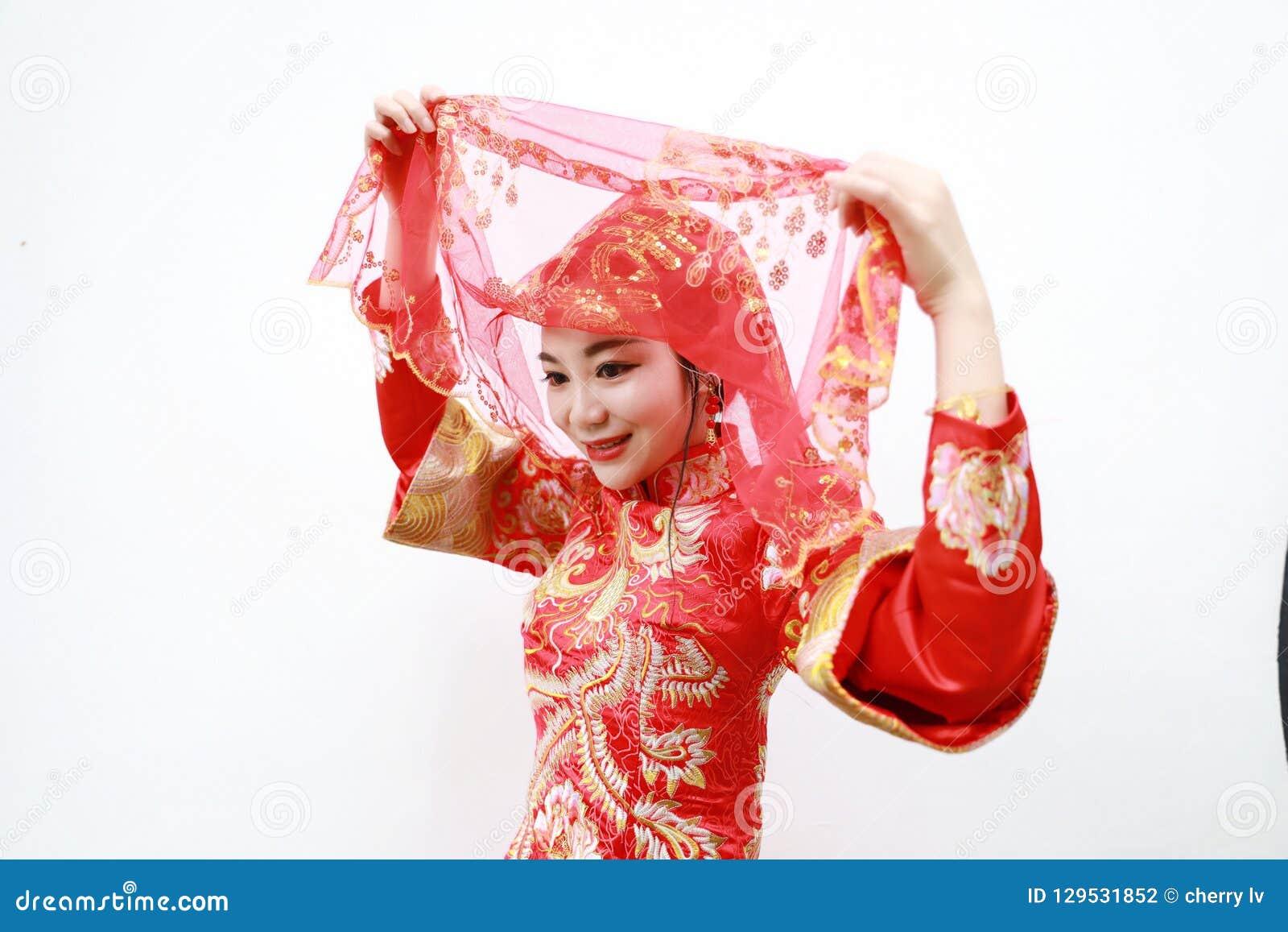 Novia hermosa china asiática bonita con el vestido rojo chino tradicional de la boda y las cubiertas principales rojas