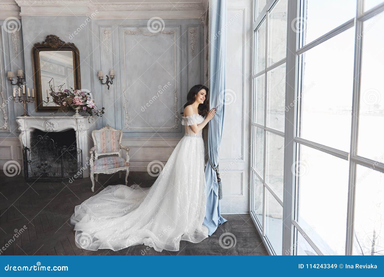 Novia hermosa, mujer morena modelo joven, en vestido de boda elegante con los hombros desnudos, con el ramo de flores adentro
