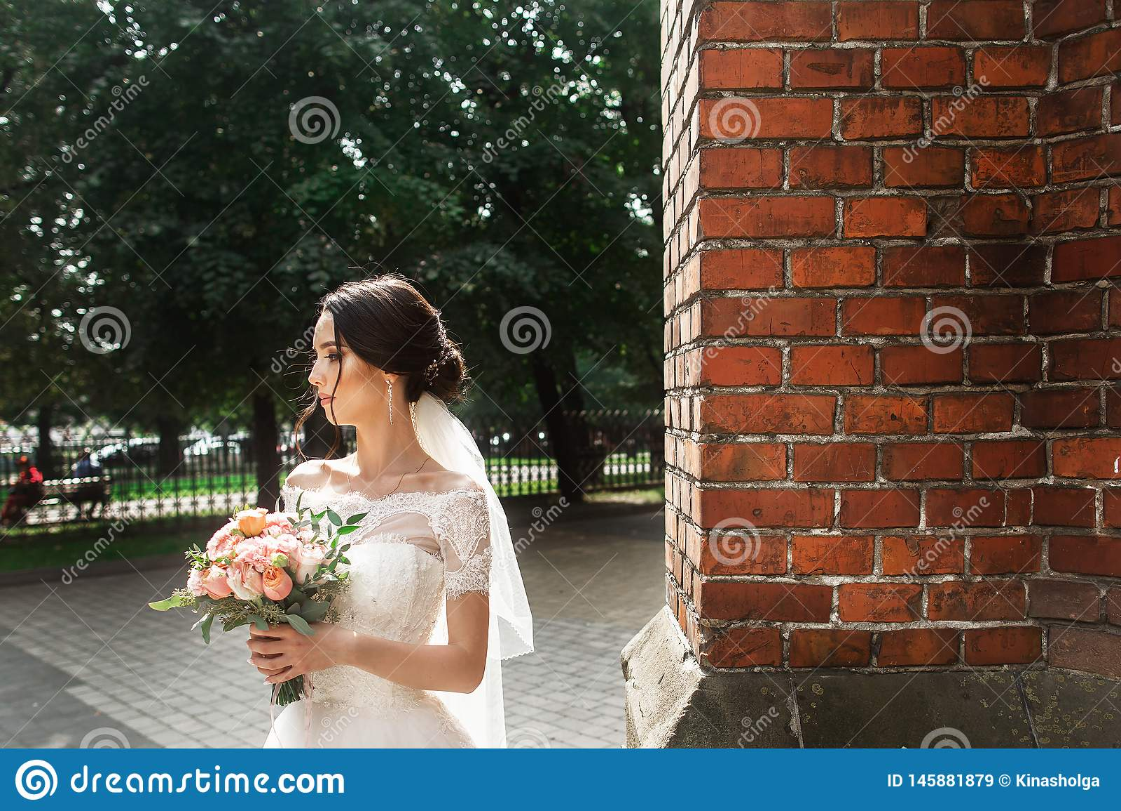 Novia hermosa que presenta cerca de la pared roja de la iglesia gótica vieja