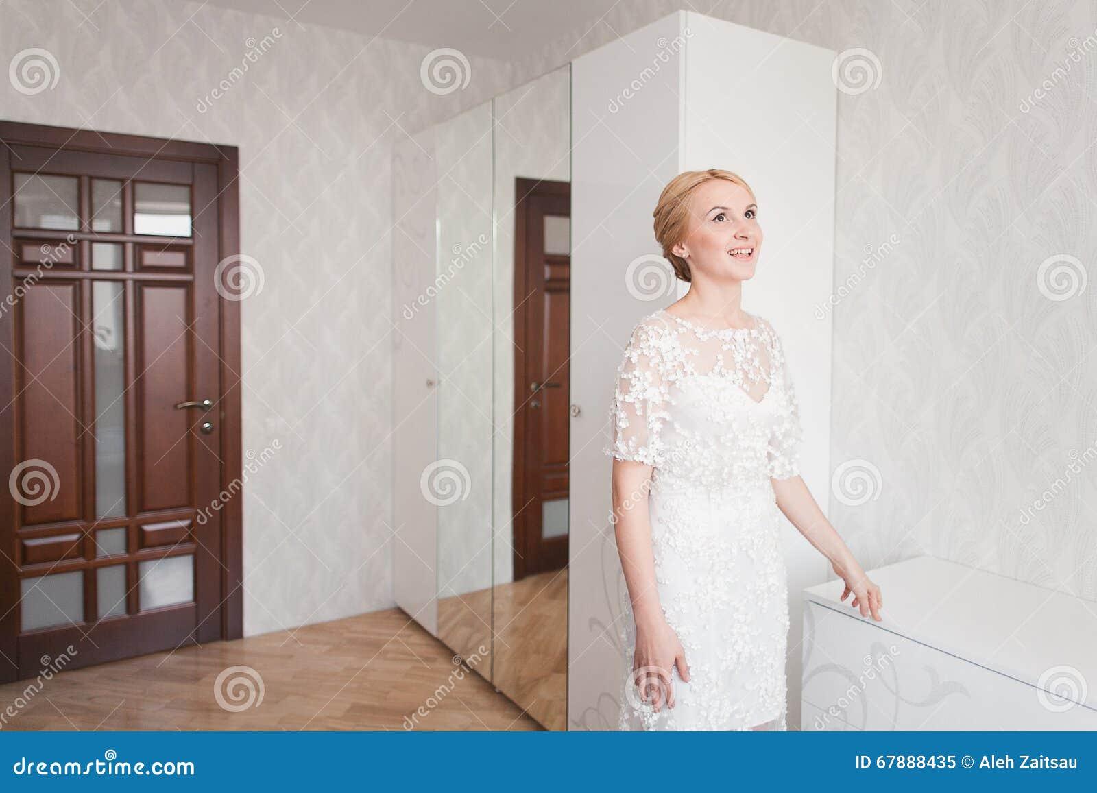Novia magnífica con maquillaje del ramo de la boda y peinado en el vestido nupcial en casa que espera al novio
