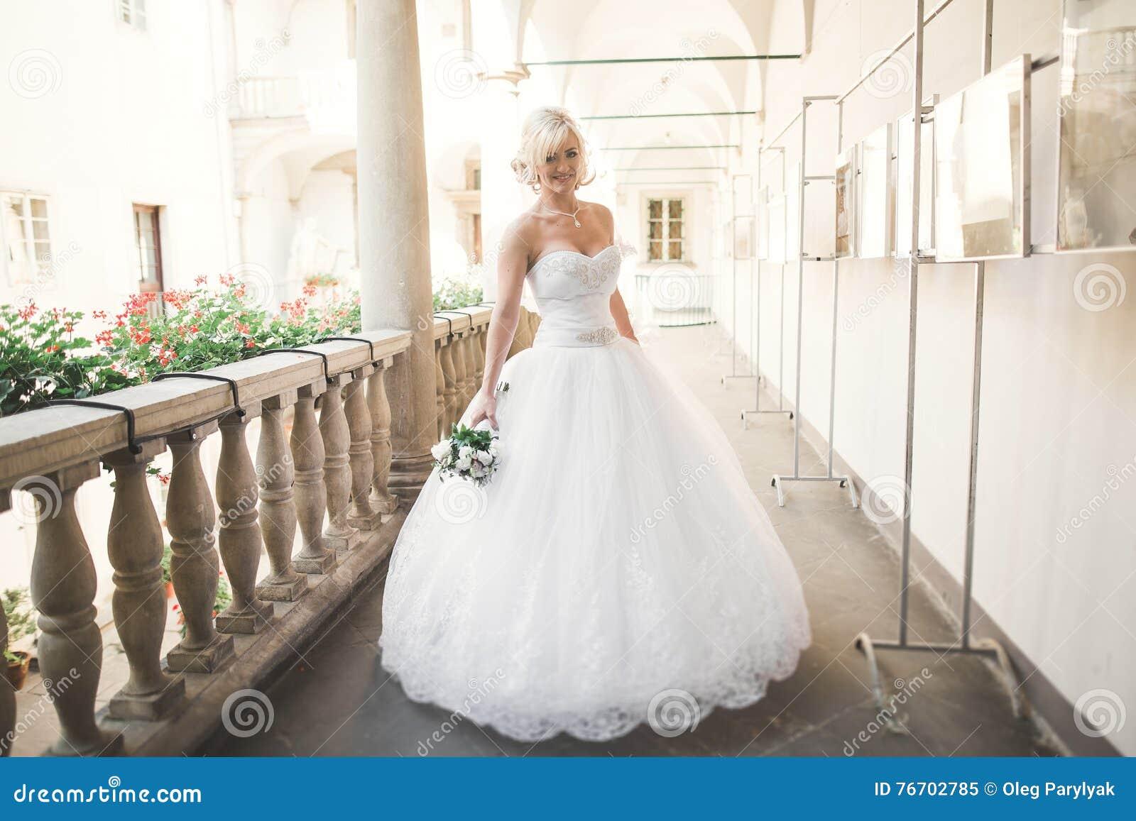 Novia maravillosa con un vestido blanco lujoso que presenta en la ciudad vieja