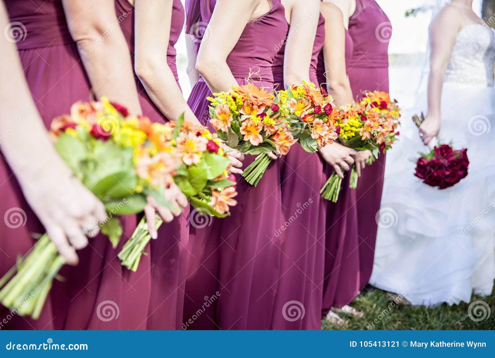 Novia y Bridemaids que sostienen ramos