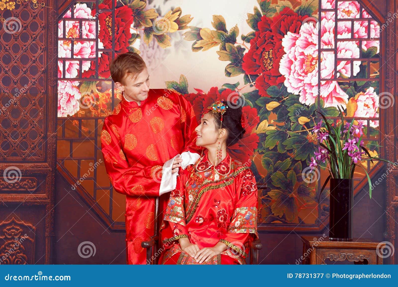 Novia y novio de la raza mixta en el estudio que lleva los equipos de la boda del chino tradicional