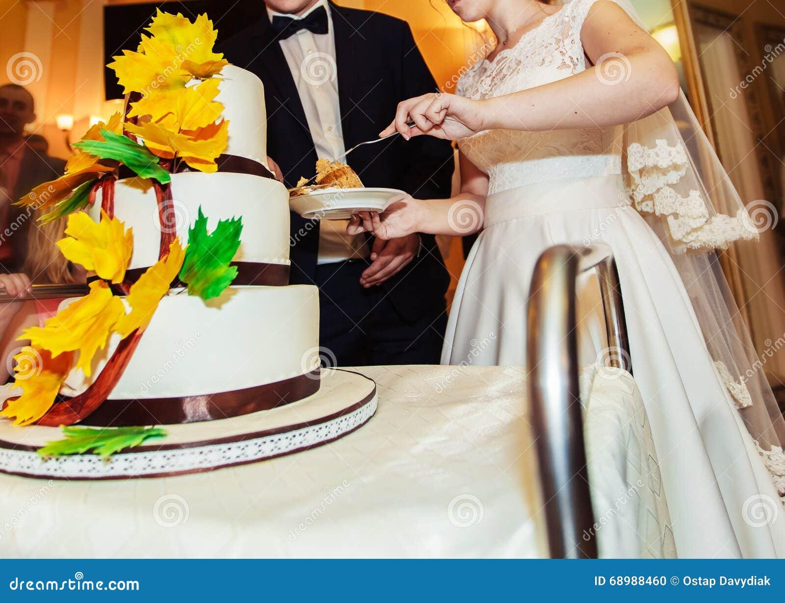 Novia y novio en la recepción nupcial que corta el pastel de bodas