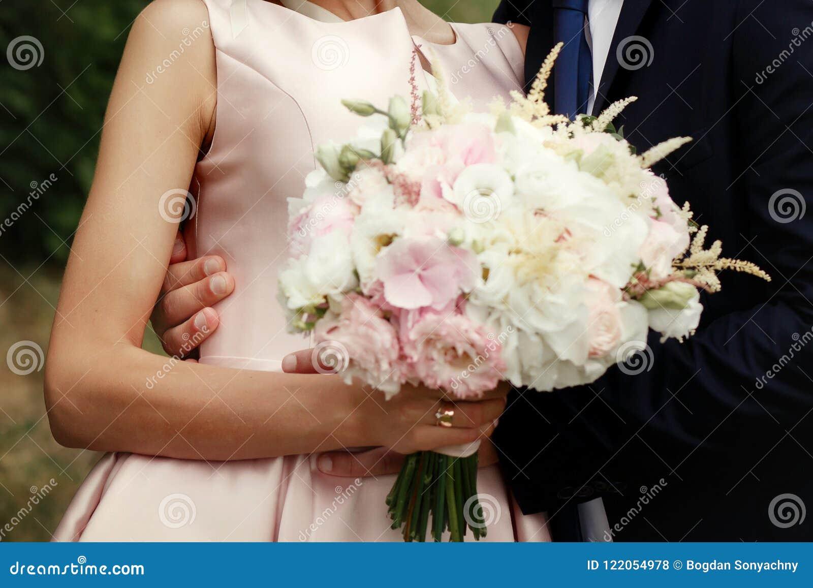 Novia y novio que abrazan, par de lujo de la boda con el bouq asombroso