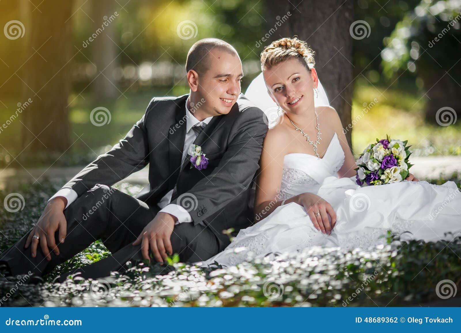 Novia y novio que abrazan y que miran a los ojos de otra sentada una hierba verde