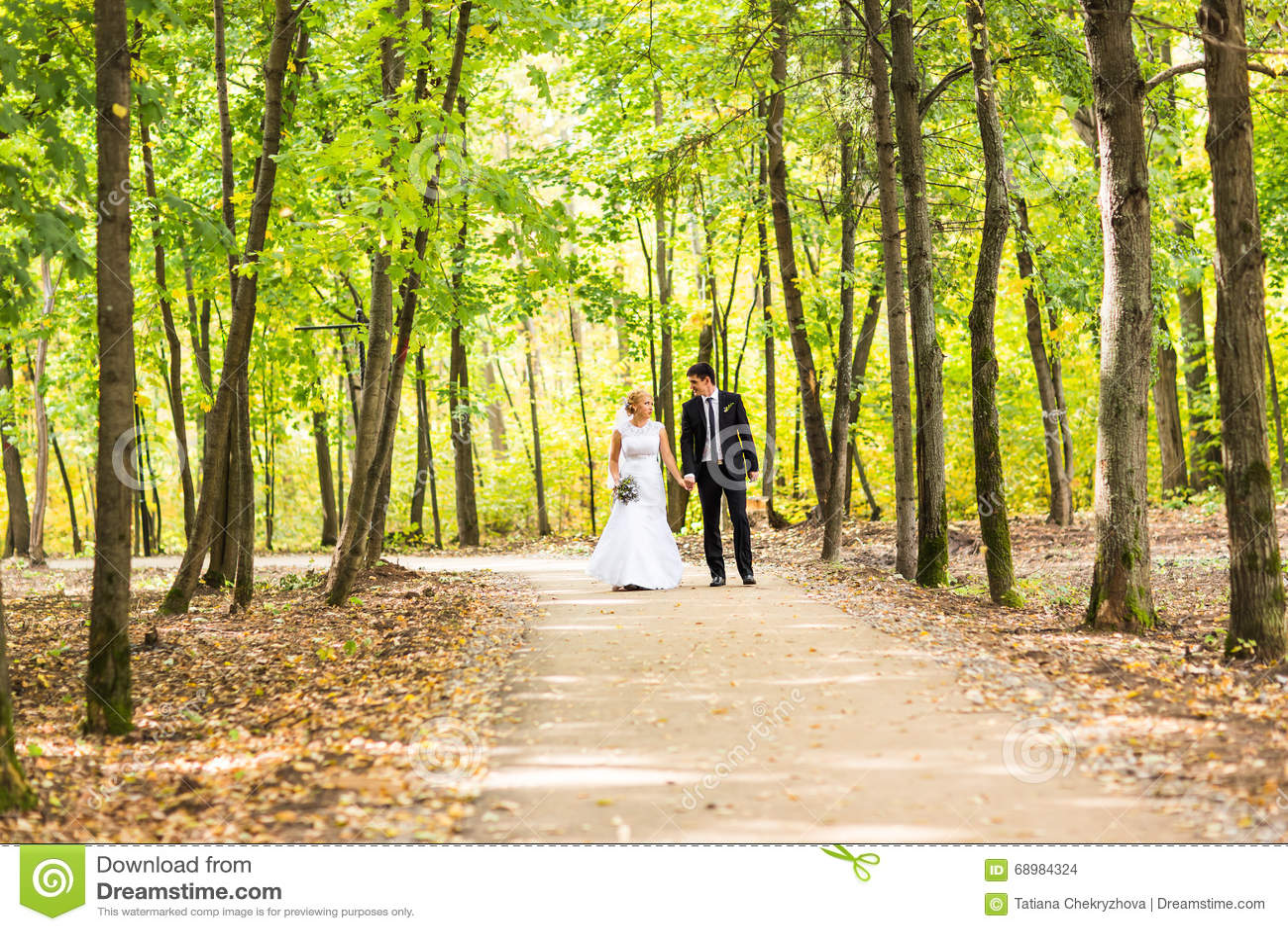 Novia y novio que llevan a cabo las manos al aire libre