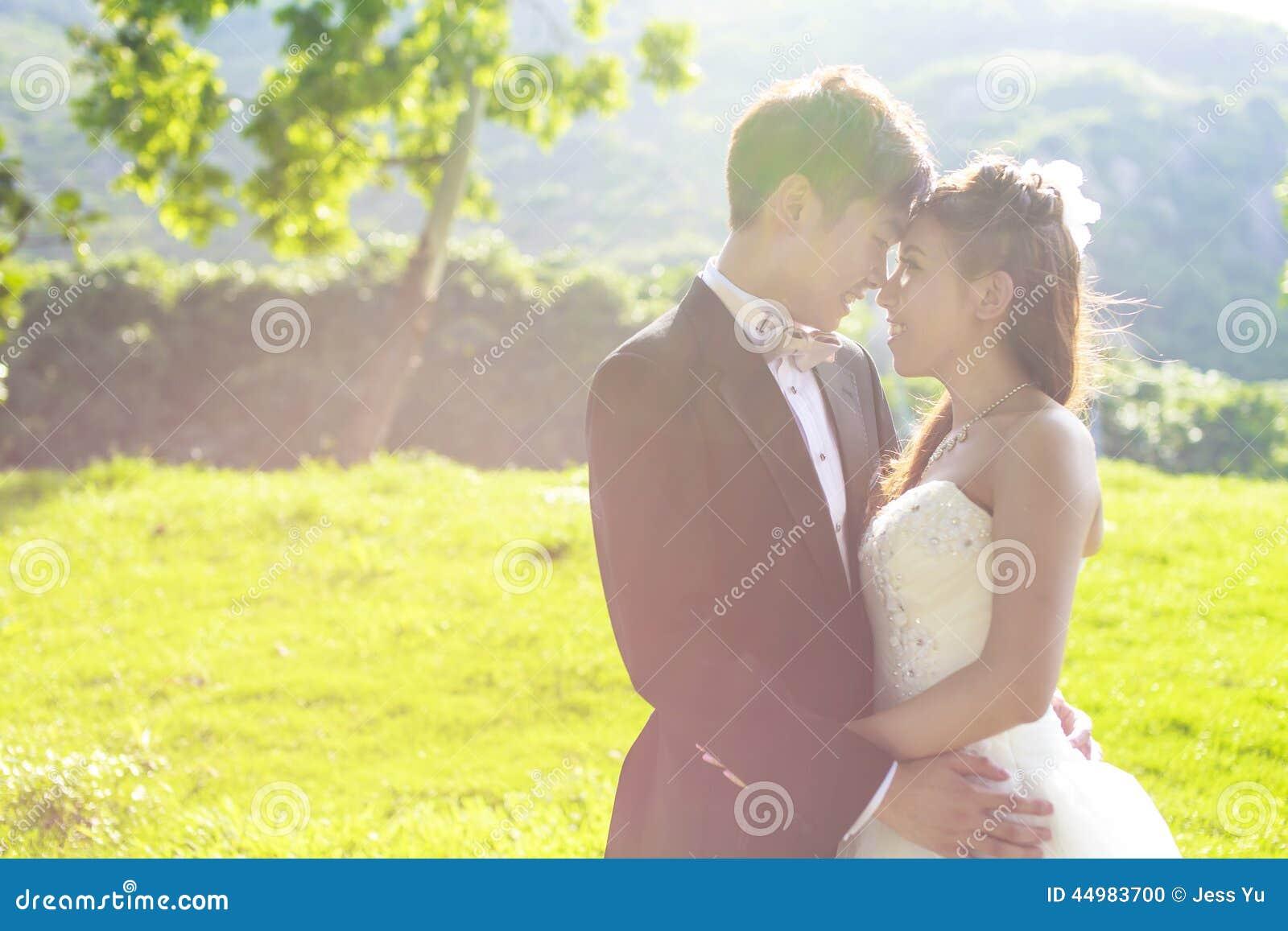 Novia y novio que rodean por luz del sol de oro natural