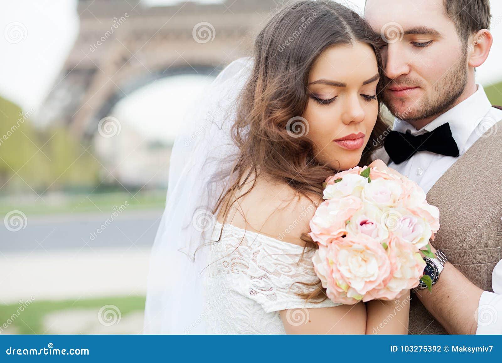 Novia y novio que se sientan en banco en parque, llevando a cabo las manos de uno a y del ramo Prepare llevar a cabo su cabeza en