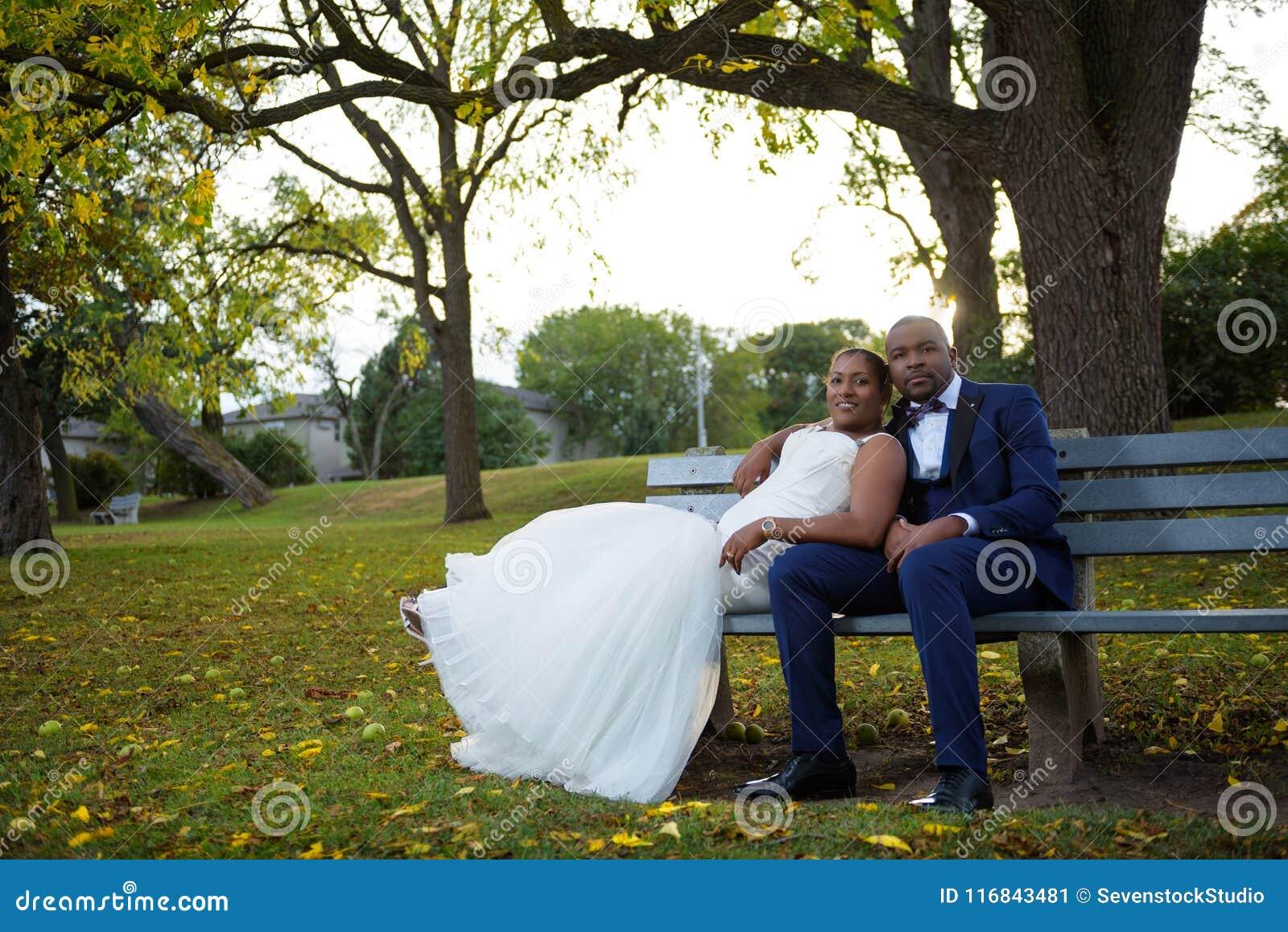 Novia y novio que se sientan en un banco de parque en la puesta del sol en un paisaje colorido