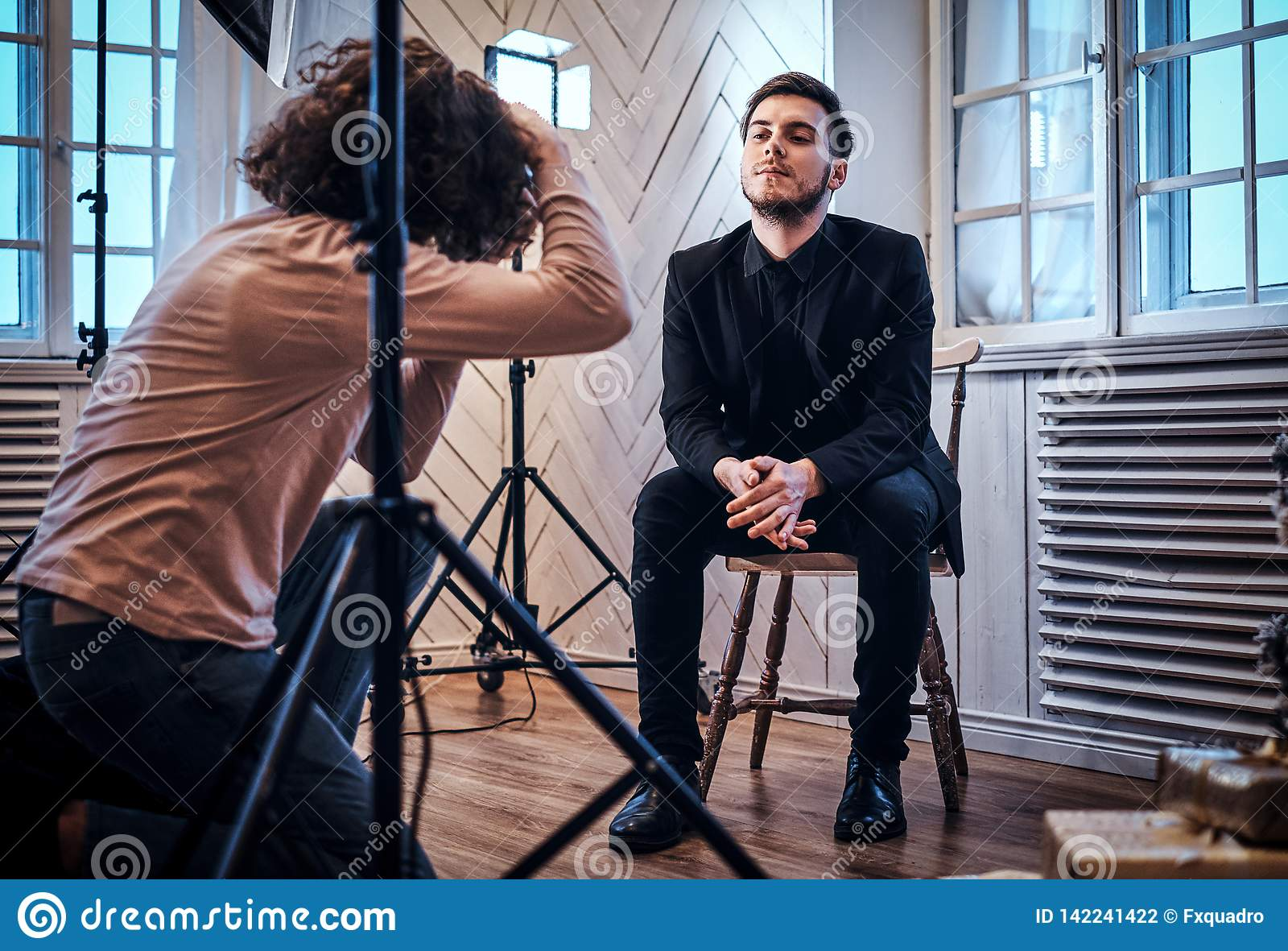 Novice photographer at a photo shoot in a studio with an elegantly dressed guy