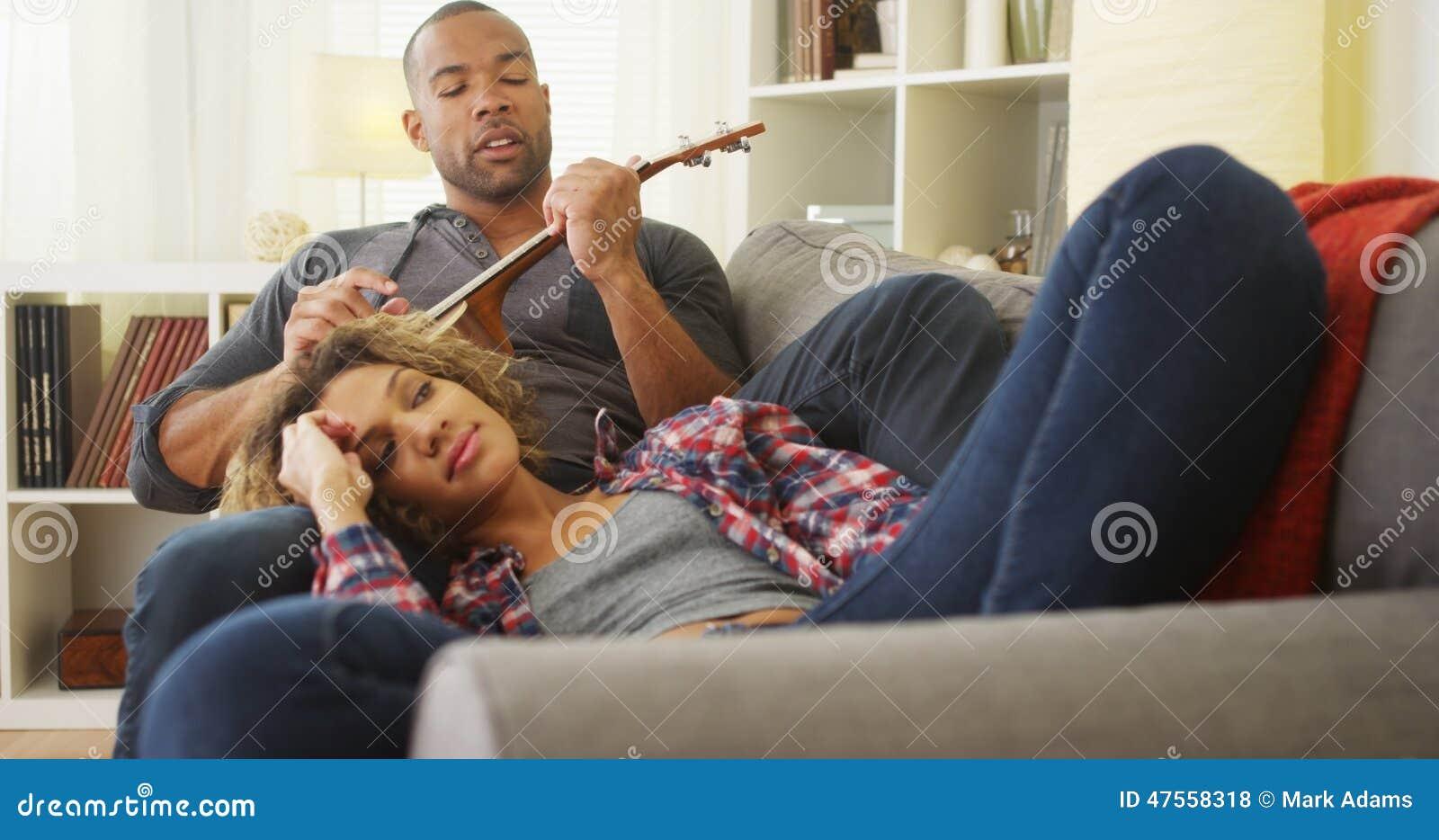Novio africano serenading su novia con el ukelele