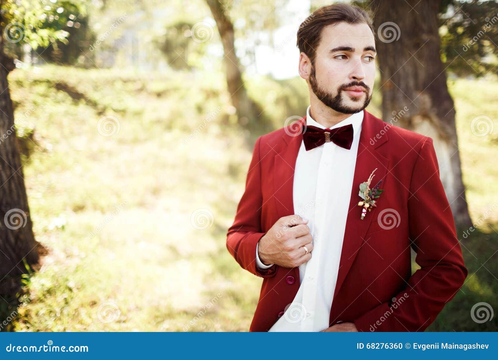 9727951964 Novio elegante en el smoking que mira el rojo ausente del marsala del  traje