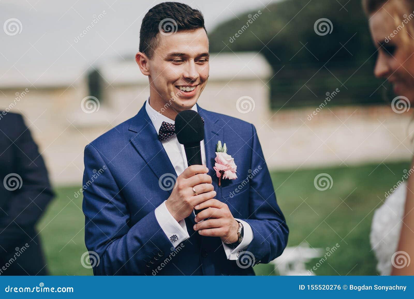 Novio elegante que pronuncia voto a su novia hermosa durante matrimonio Novio que pronuncia discurso y que sostiene el micrófono