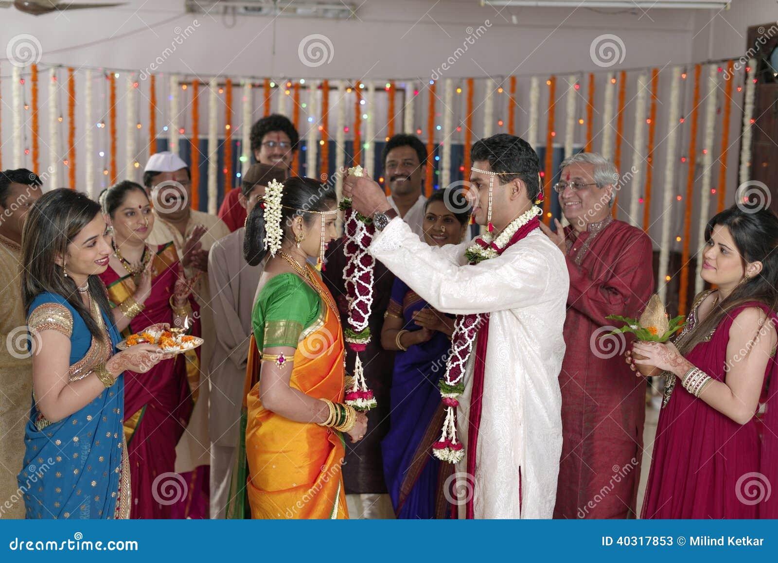 Novio hindú indio que mira a la novia y que intercambia la guirnalda en la boda del maharashtra