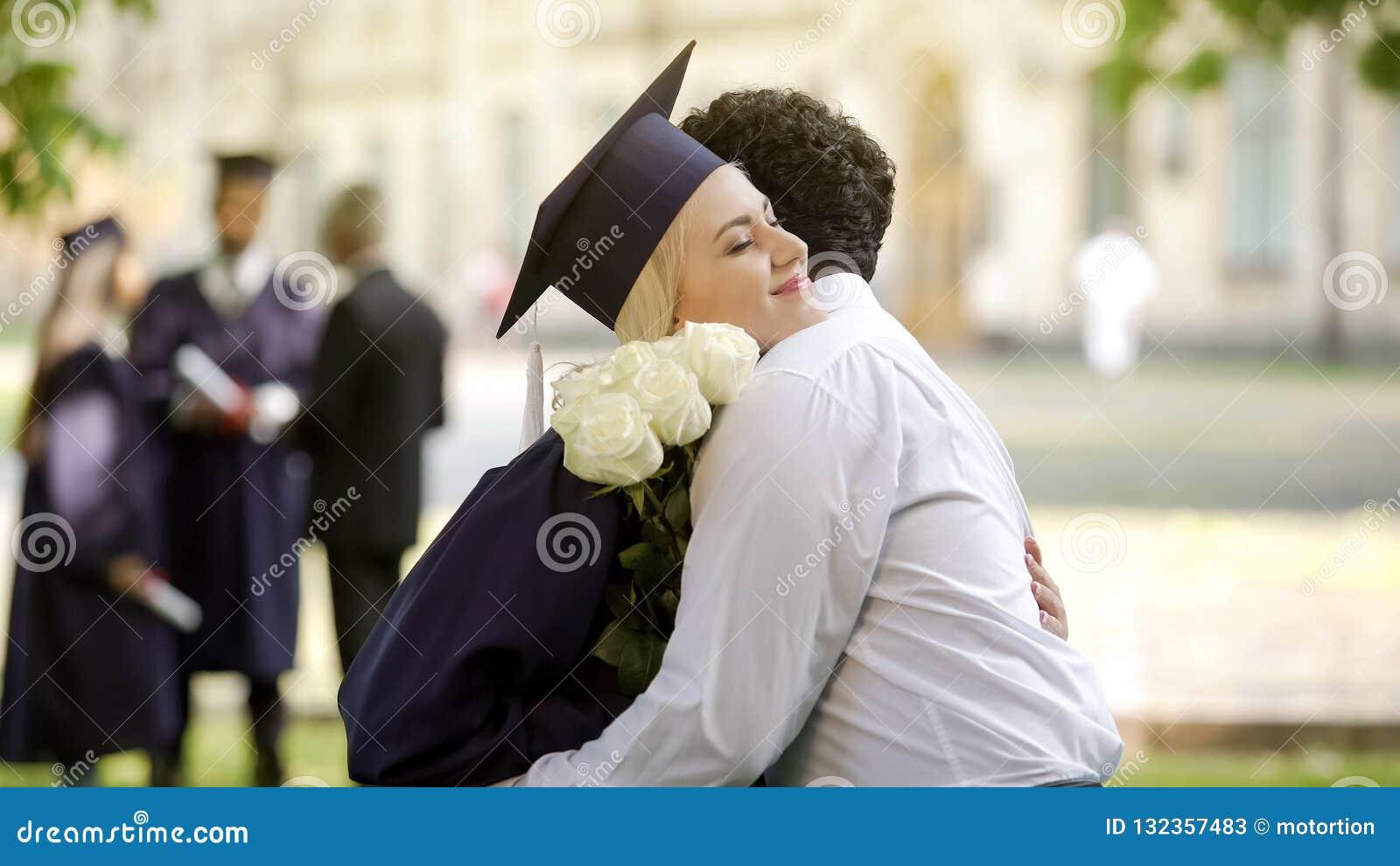 fbe42e4d1 Novio que da a flores el suyo la novia del graduado y que abraza la ocasión