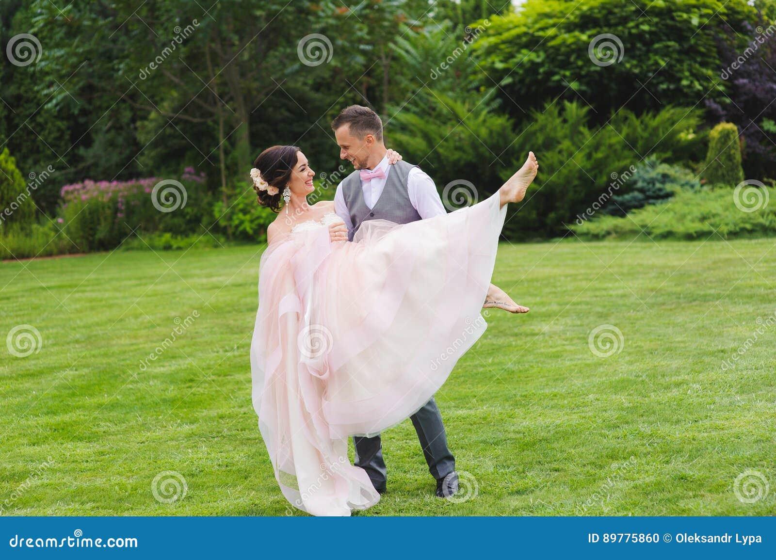 Novio que detiene a la novia hermosa en sus brazos