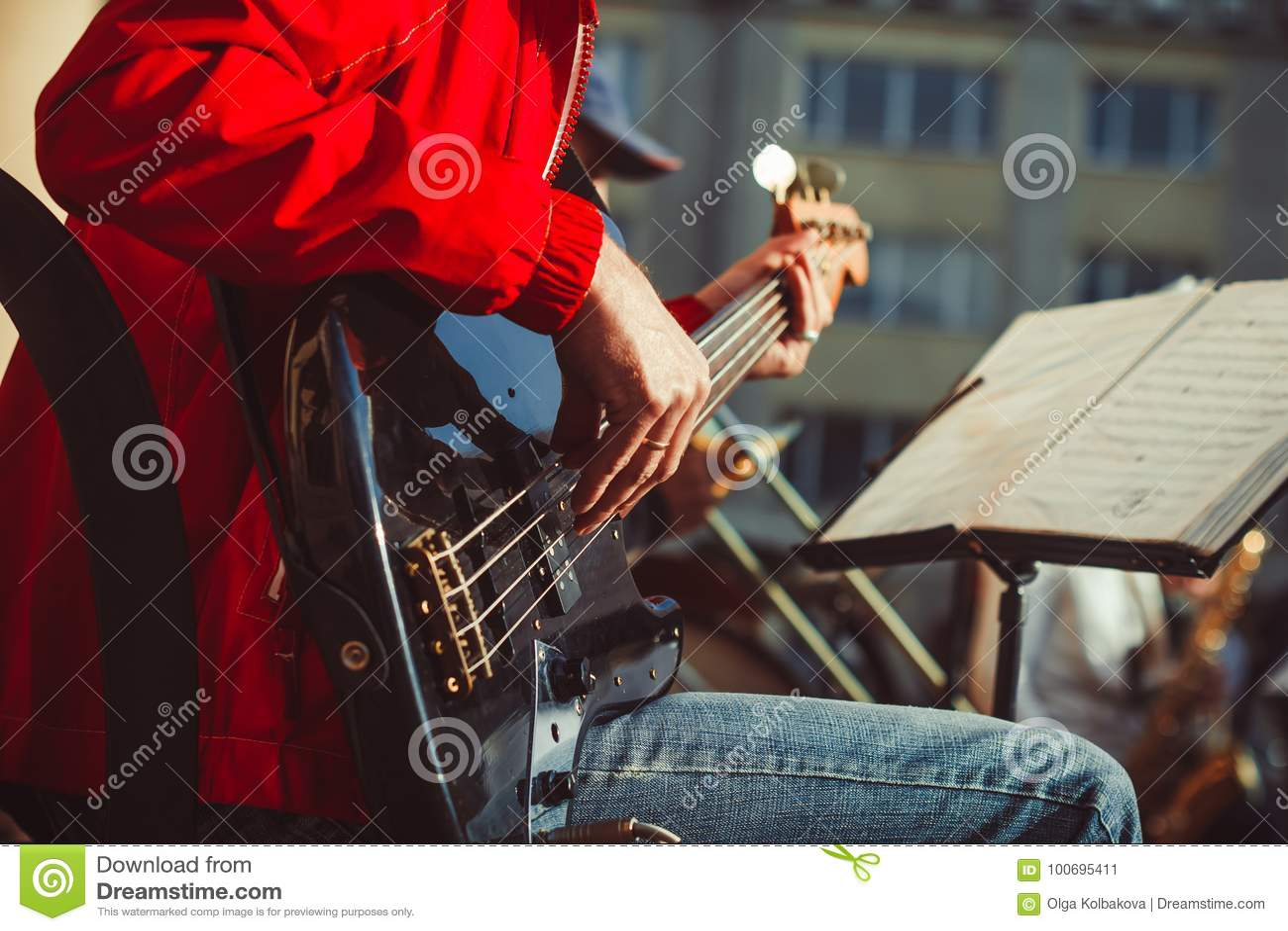 Novokuzneck, Russland - 13 08 2017: die Bassgitarristspiele in einem Orchester auf der Straße