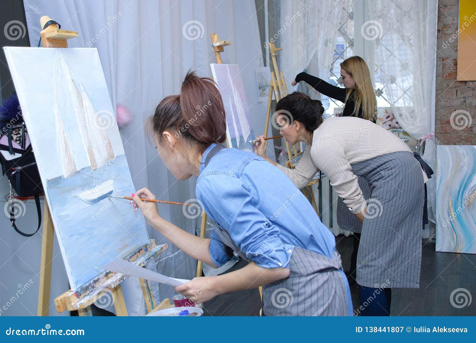 Novosibirsk 02-24-2018 Ocupação na oficina da arte As meninas pintam imagens com pintura acrílica na lona