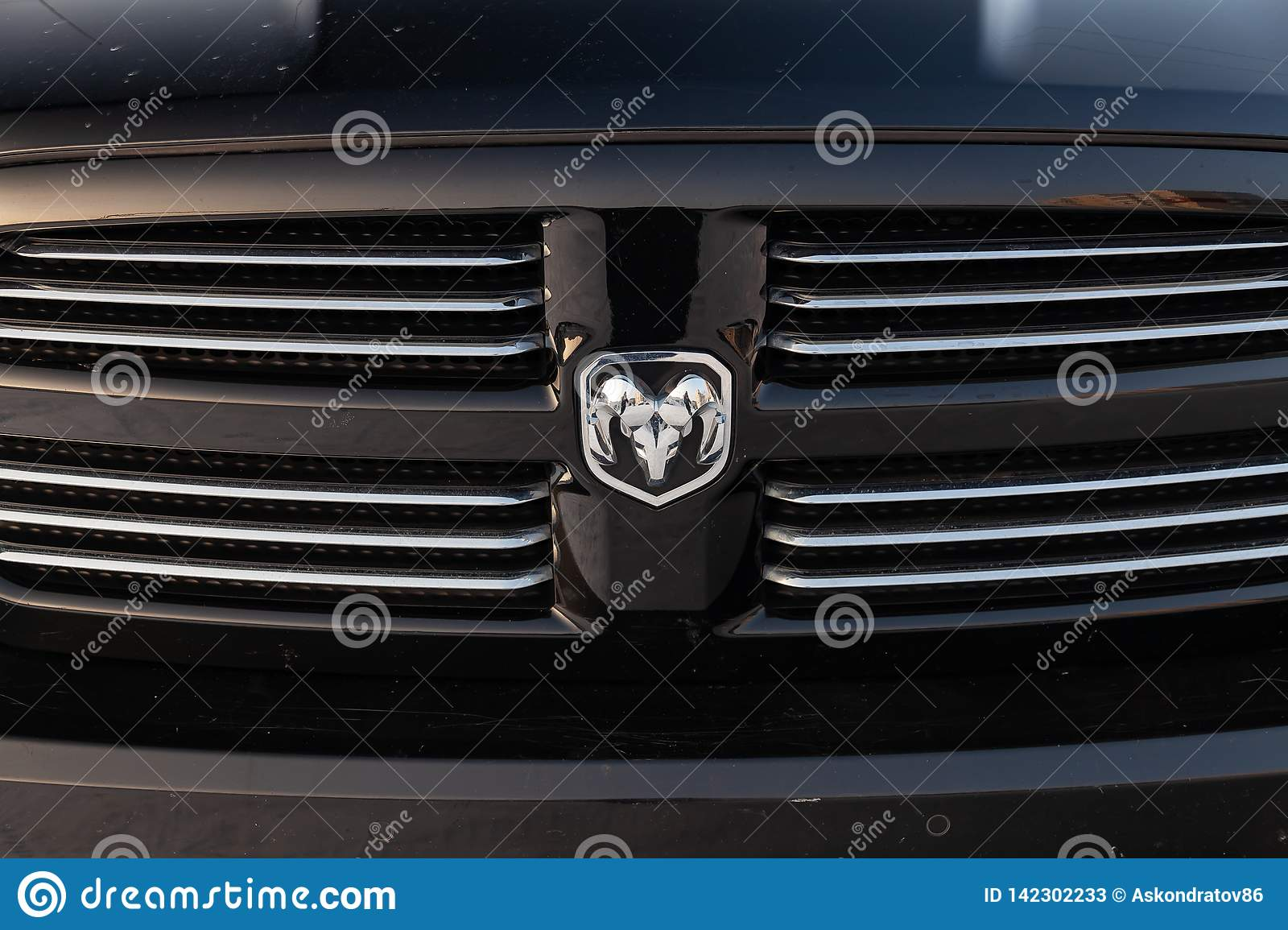 Black Dodge Ram with an engine of 5.7 liters front radiator grille view on the car parking with snow background