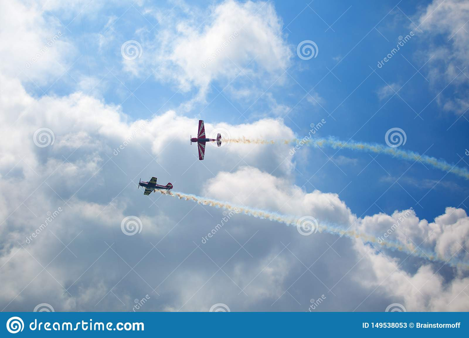 Mochishche airfield, local air show, two Yak-52, aerobatic team `Open Sky`, Barnaul, on blue sky with clouds background
