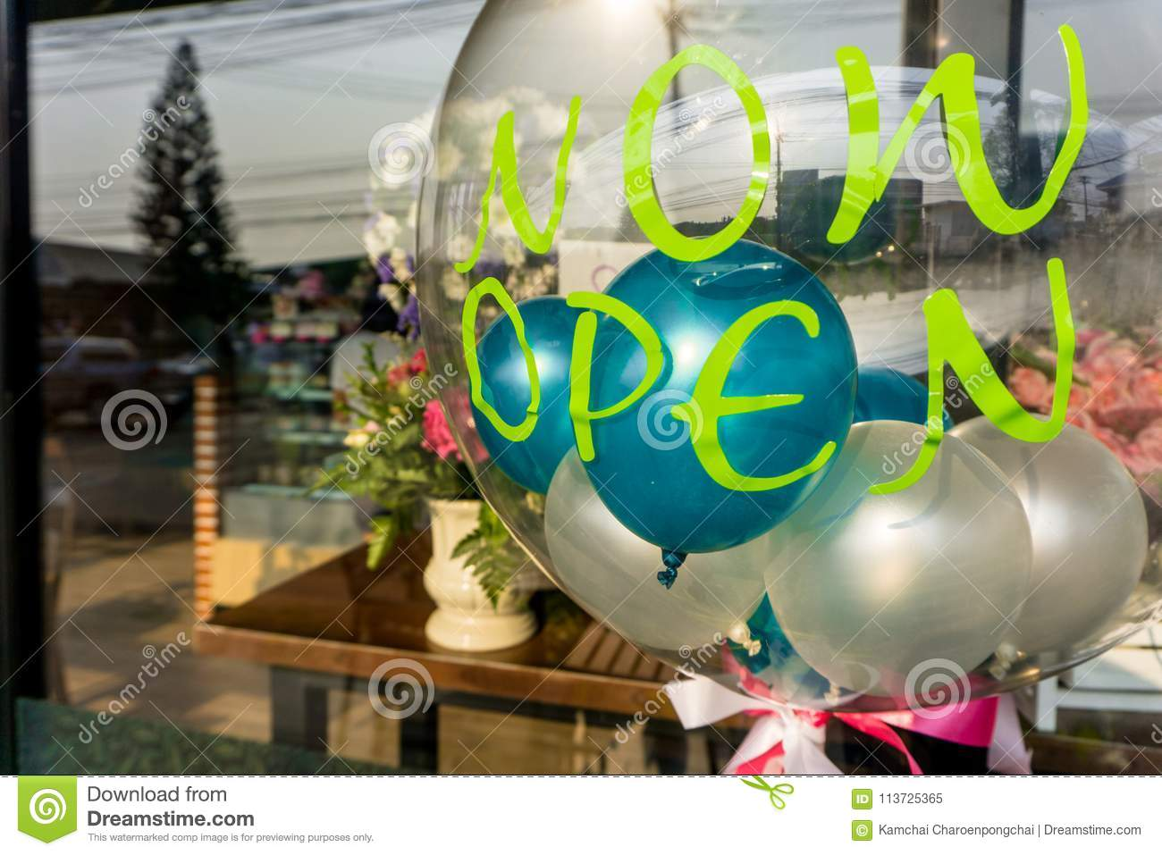 `Now Open` sticker on transparent balloon with other small colourful balloons inside.