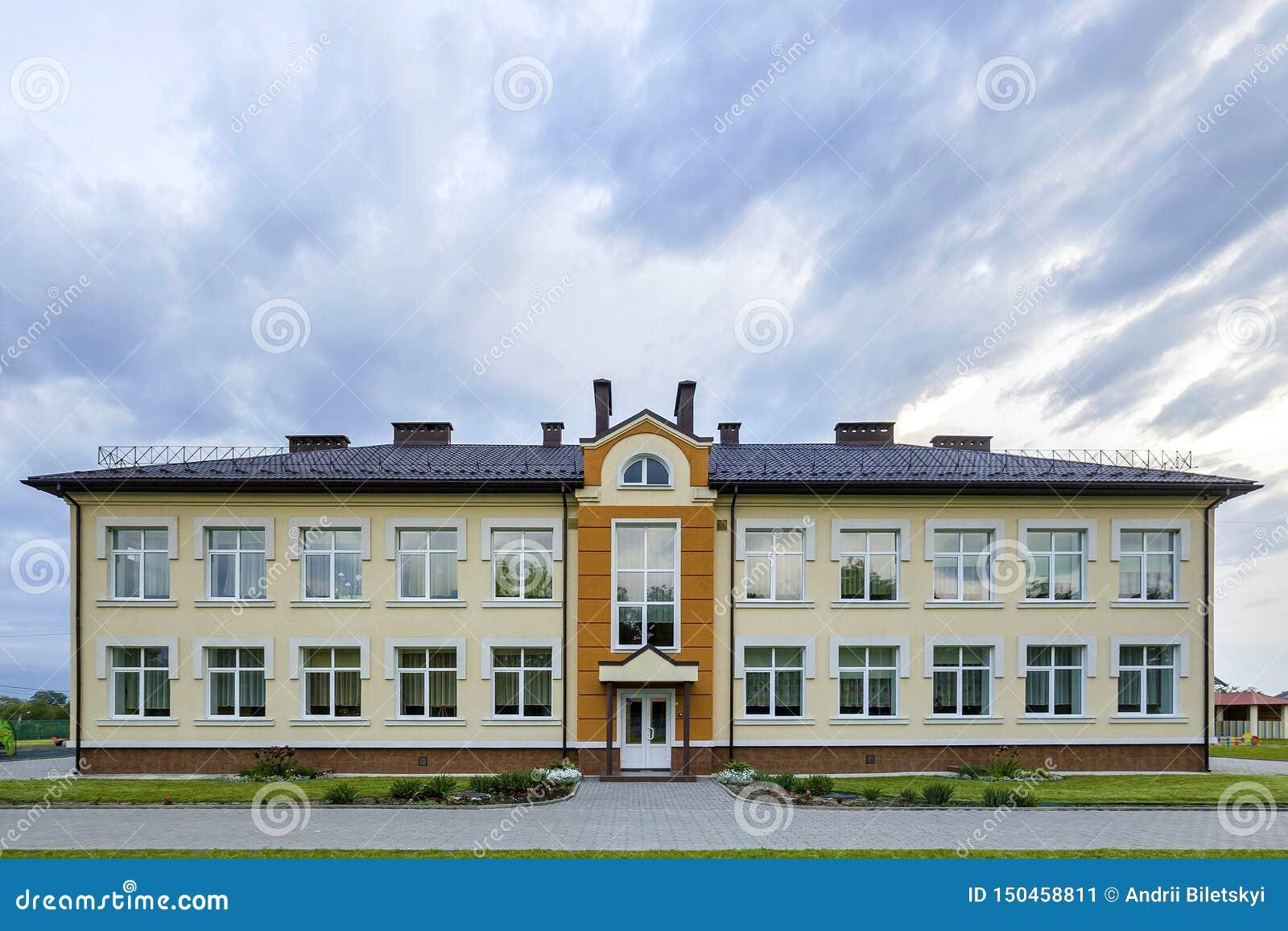 Nowego nowożytnego jednopiętrowego dziecina preschool budynek z dużymi okno na zielonej trawiastej gazonu i niebieskiego nieba ko