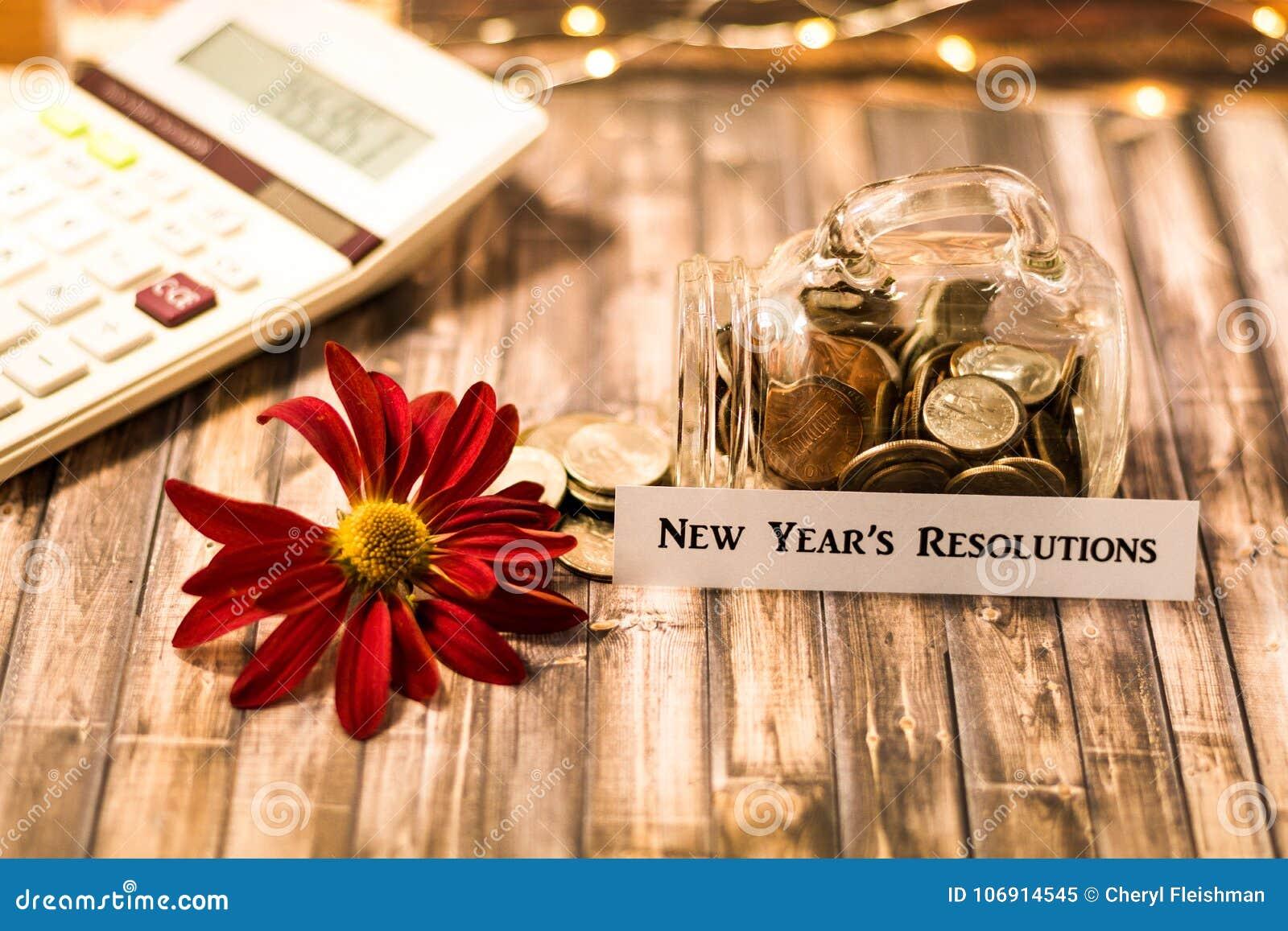 Nowego Roku ` s postanowienia pieniądze słoju savings motywacyjny pojęcie na drewnianej desce