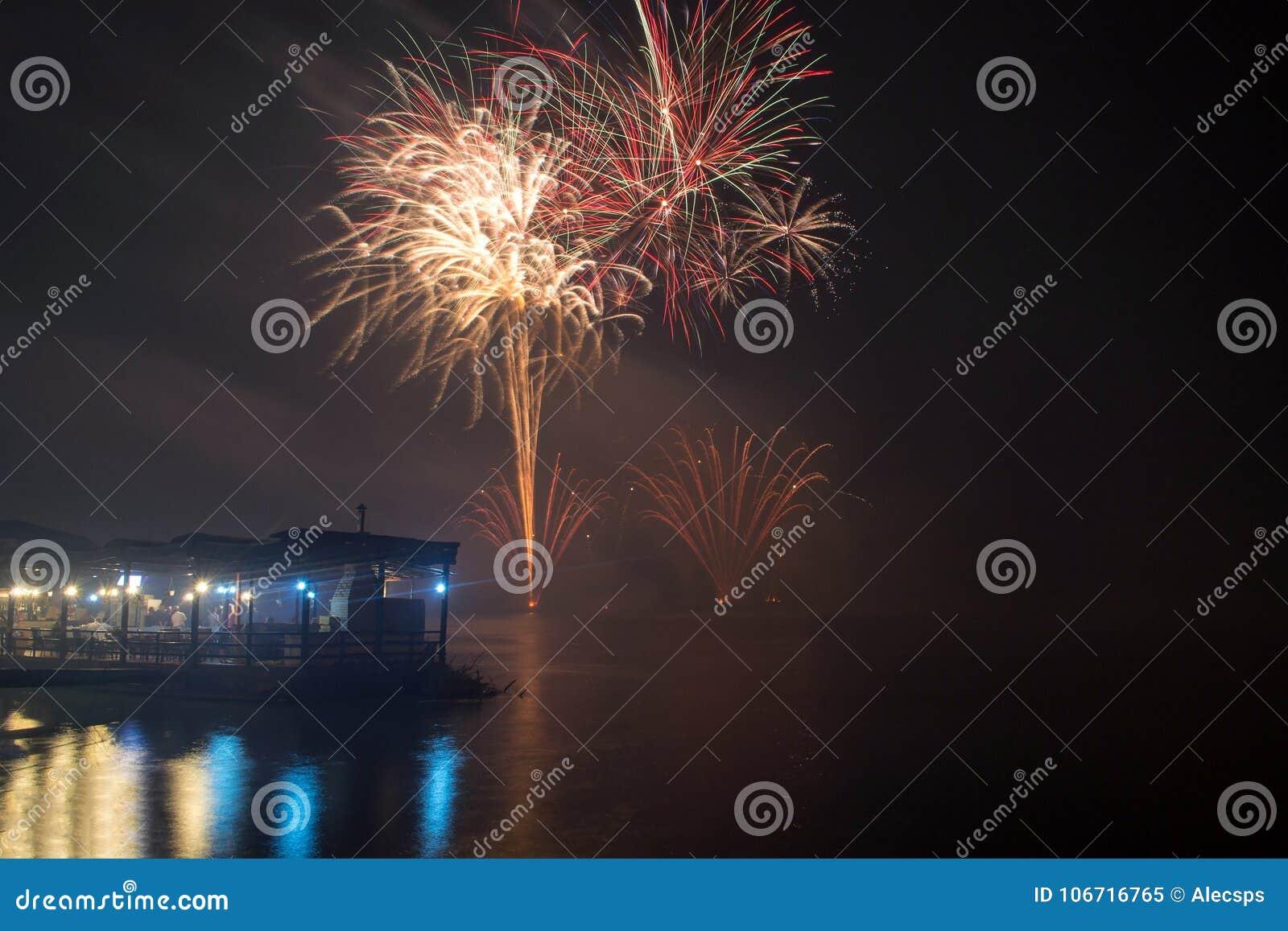 Nowego Roku ` s wigilii fajerwerki wszczynający od wody z odbiciami