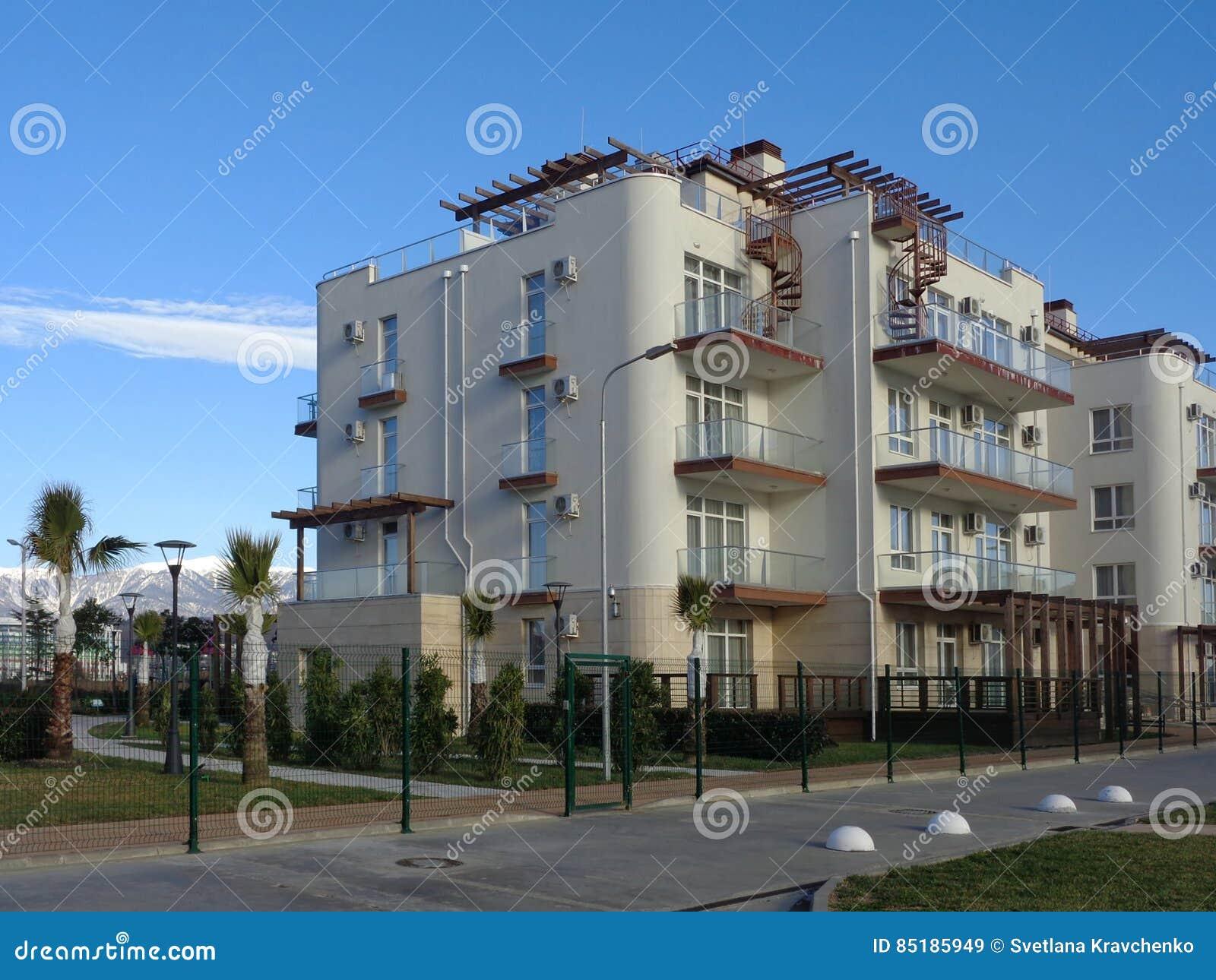 Nowi budynki mieszkaniowi z zielonym gazonem za ogrodzeniem